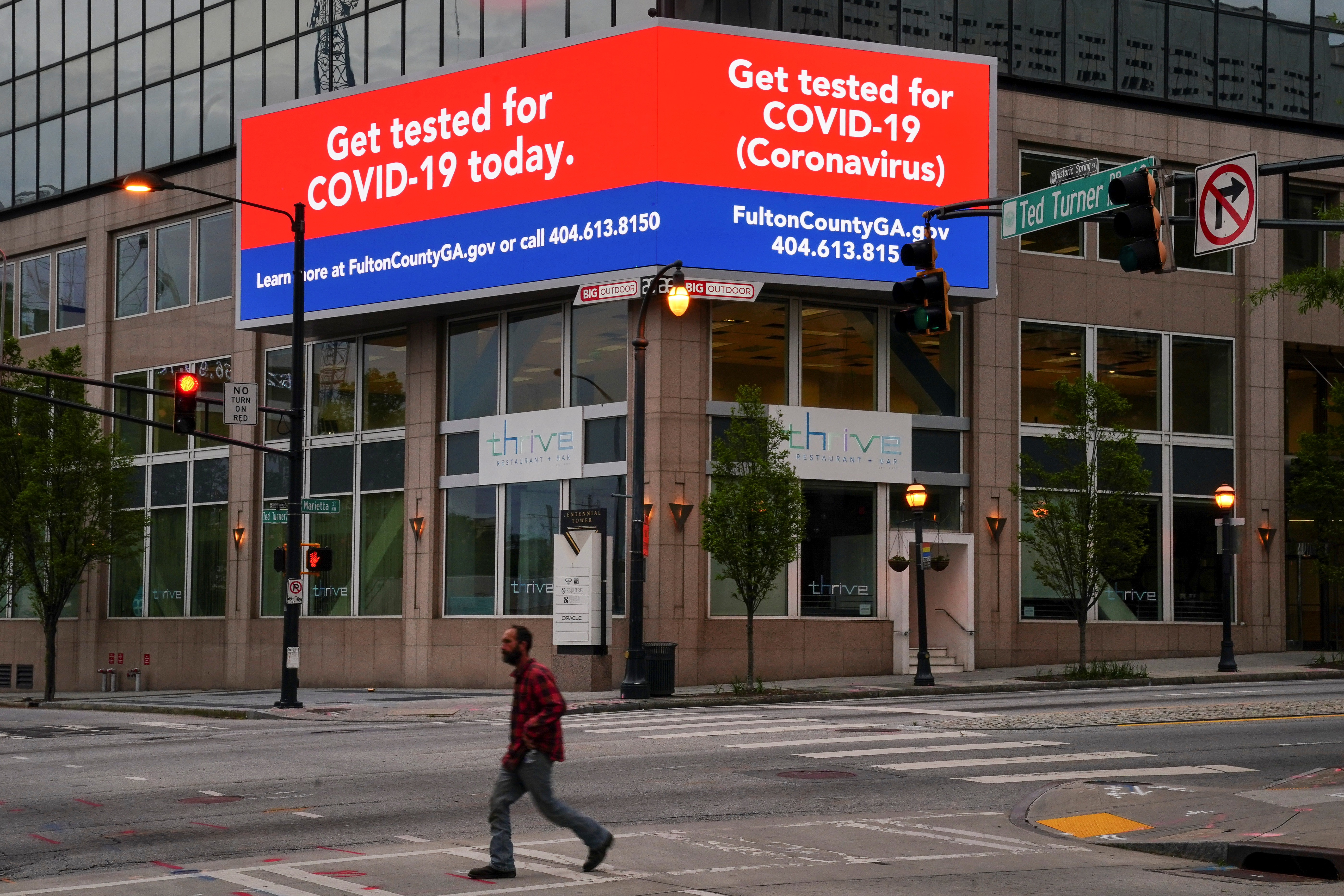 A man walks in front of a sign encouraging the public to get tested for COVID-19, days before the phased reopening of businesses and restaurants from coronavirus disease (COVID-19) restrictions in Atlanta, Georgia, U.S. April 22, 2020. REUTERS/Elijah Nouvelage