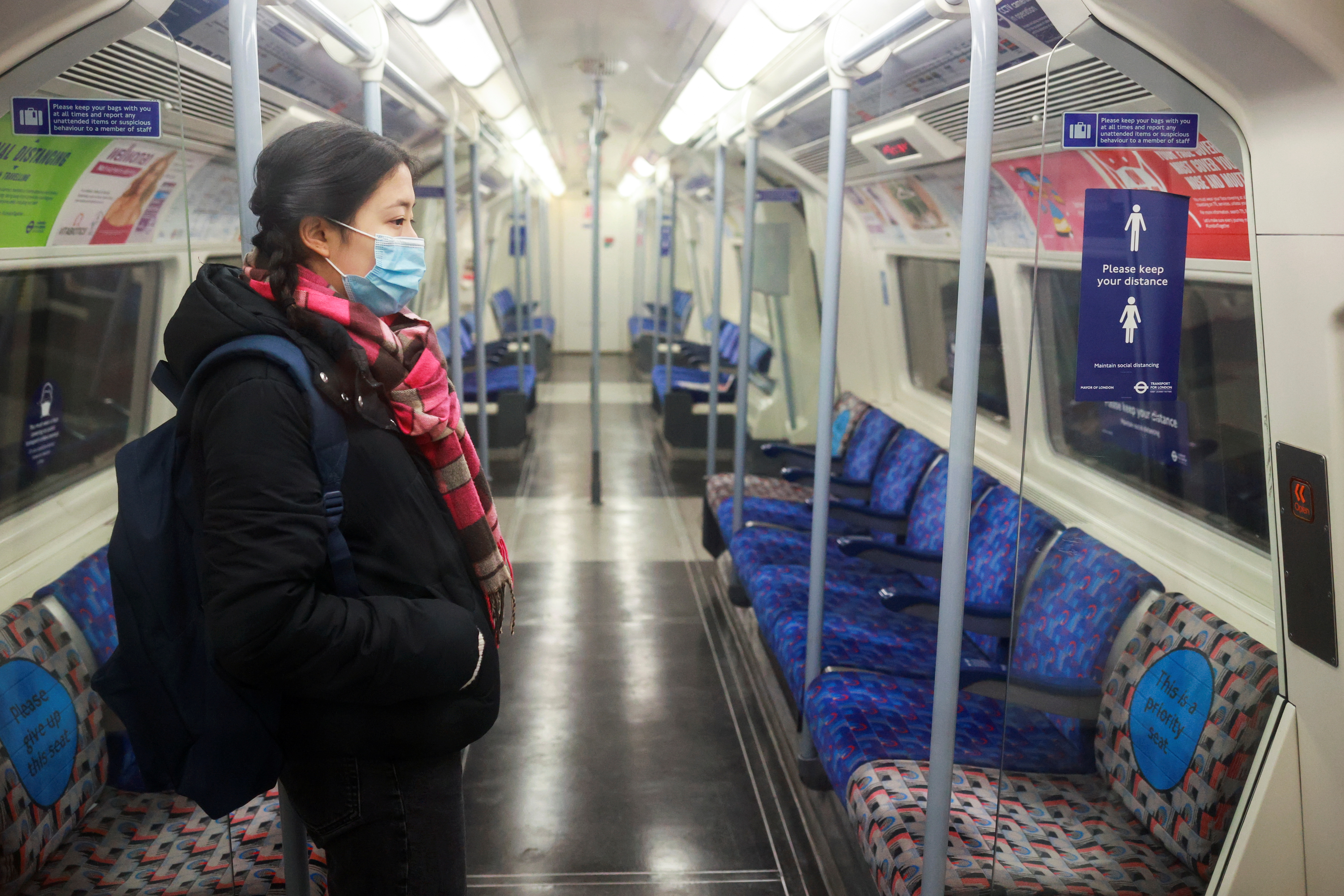 A woman stand inside an almost deserted underground train, amid the coronavirus disease (COVID-19) outbreak, in London, Britain, January 5, 2021. REUTERS/Hannah McKay