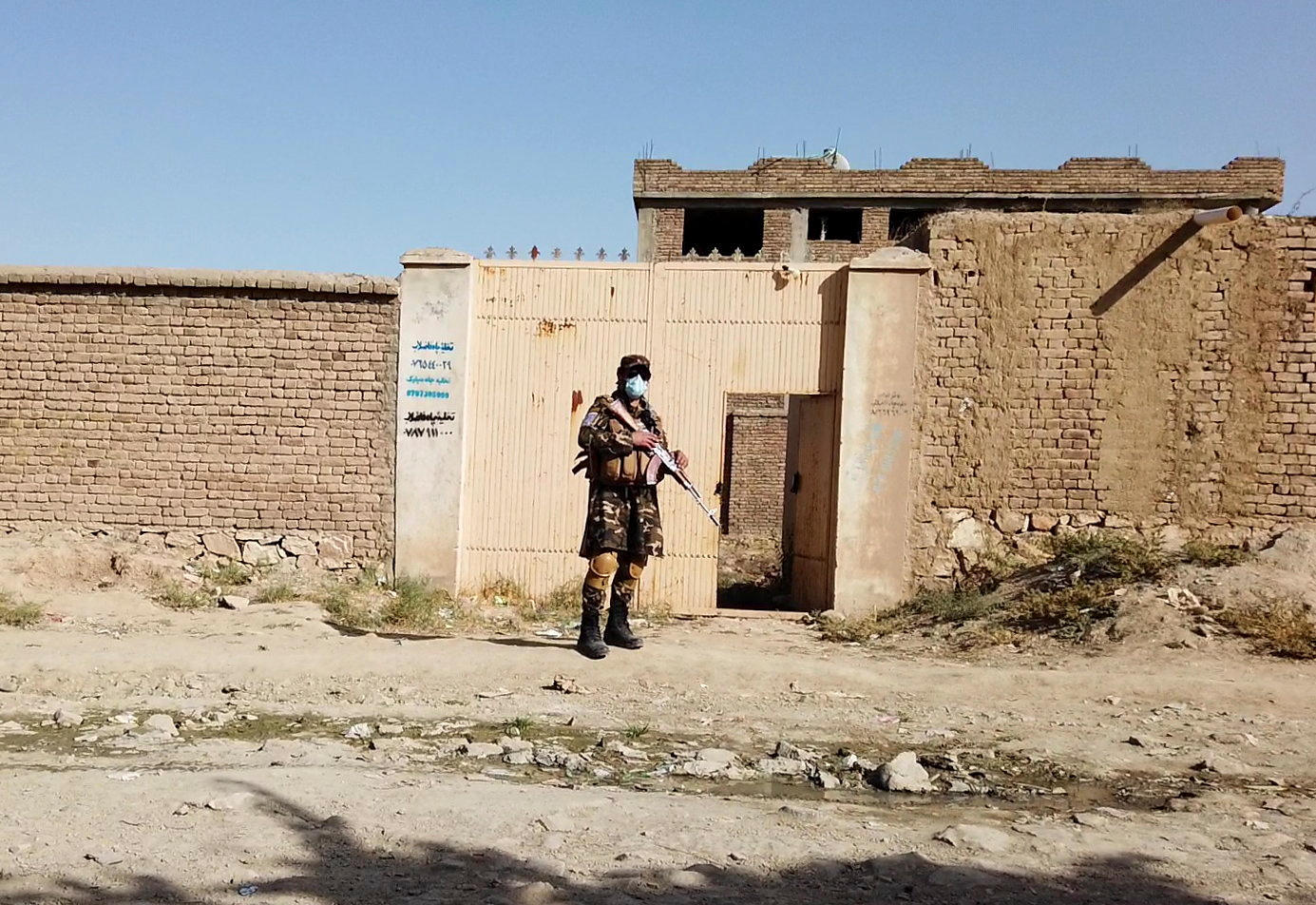 A Taliban solider stands guard in front of a house neighbouring the Islamic State hideout raided by Taliban forces on Sunday night in northern Kabul, Afghanistan October 4, 2021. REUTERS/Staff