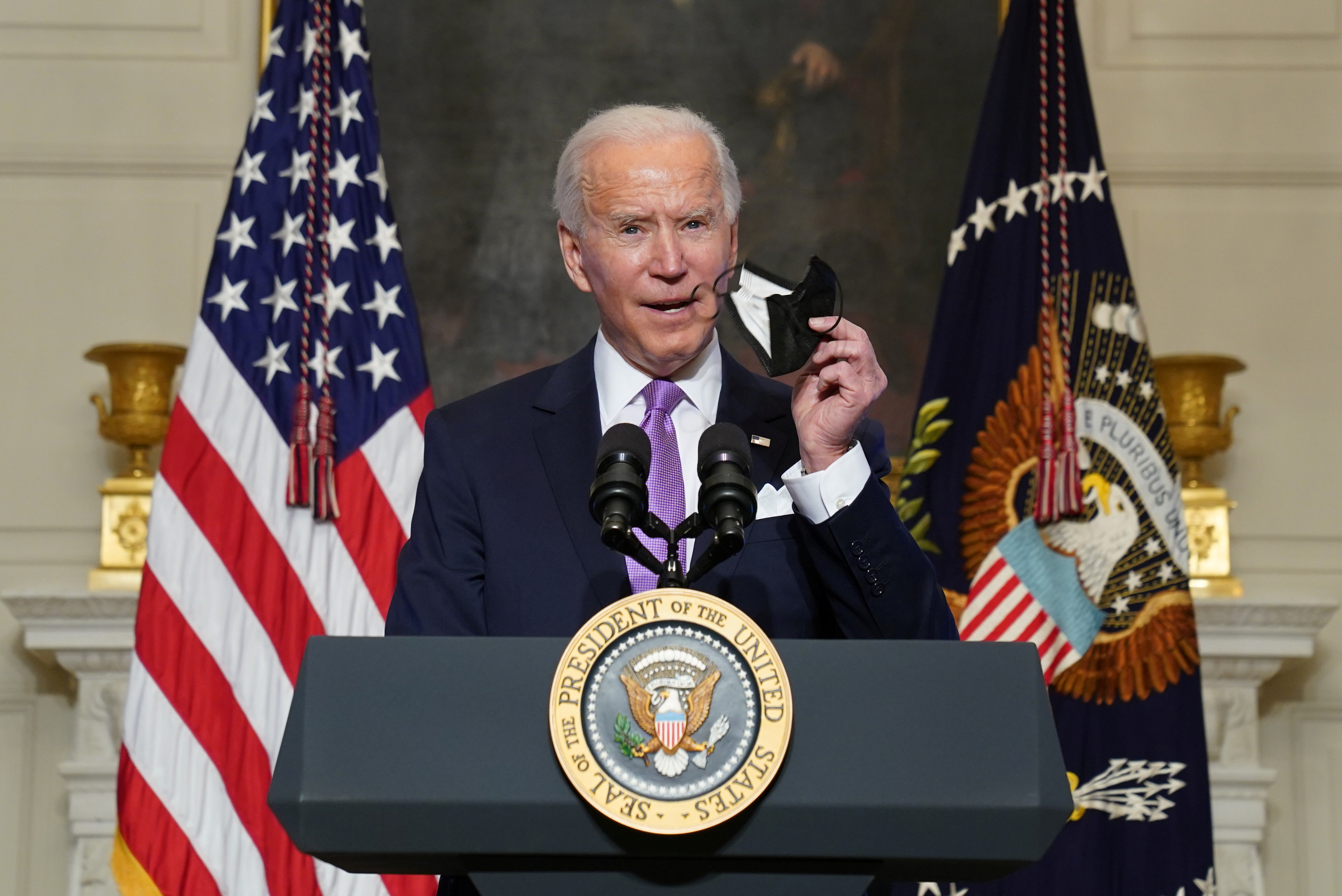 U.S. President Joe Biden holds up a face mask as he speaks about the fight to contain the coronavirus disease (COVID-19) pandemic, at the White House in Washington, U.S. January 26, 2021. REUTERS/Kevin Lamarque