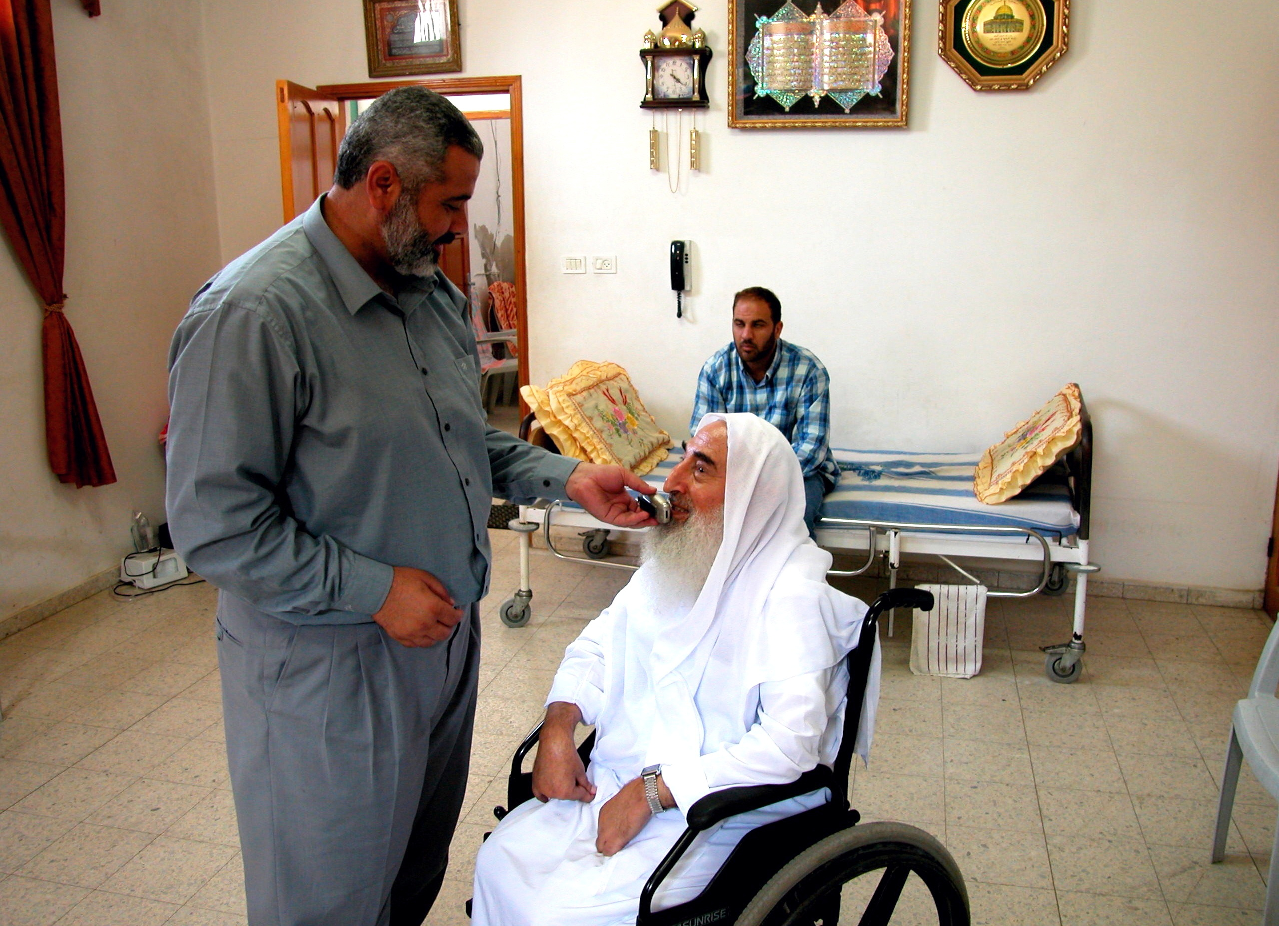 Palestinian Hamas official Ismail Haniyeh assists Hamas co-founder Ahmed Yassin in taking a phone call in Gaza City, Palestinian Territories June 13, 2003. Picture taken June 13, 2003. REUTERS/Stephen Farrell/Files