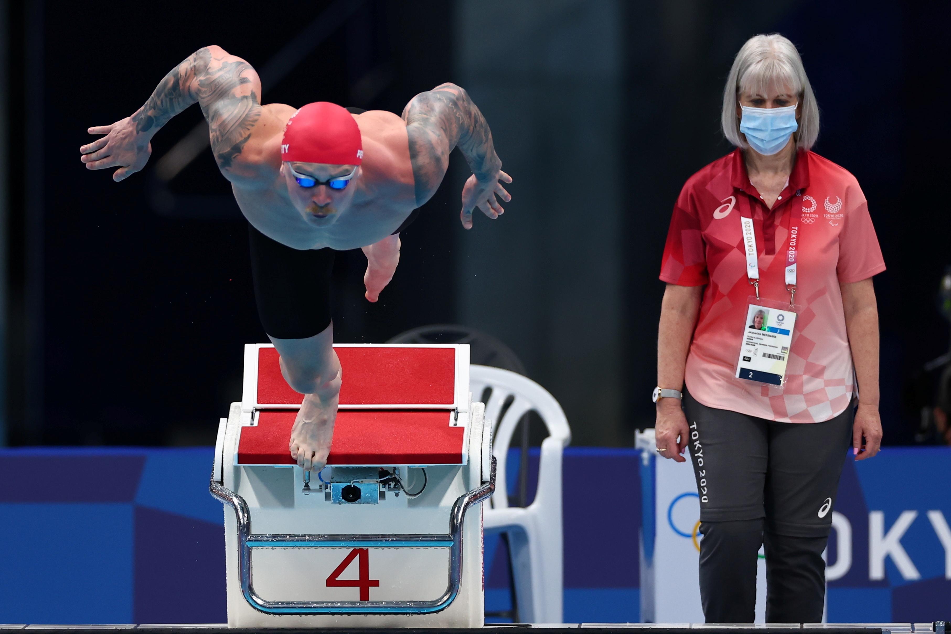 Tokyo 2020 Olympics - Swimming - Men's 100m Breaststroke - Heats - Tokyo Aquatics Centre - Tokyo, Japan - July 24, 2021. Adam Peaty of Britain in action as a referee wearing a mask looks on REUTERS/Kai Pfaffenbach
