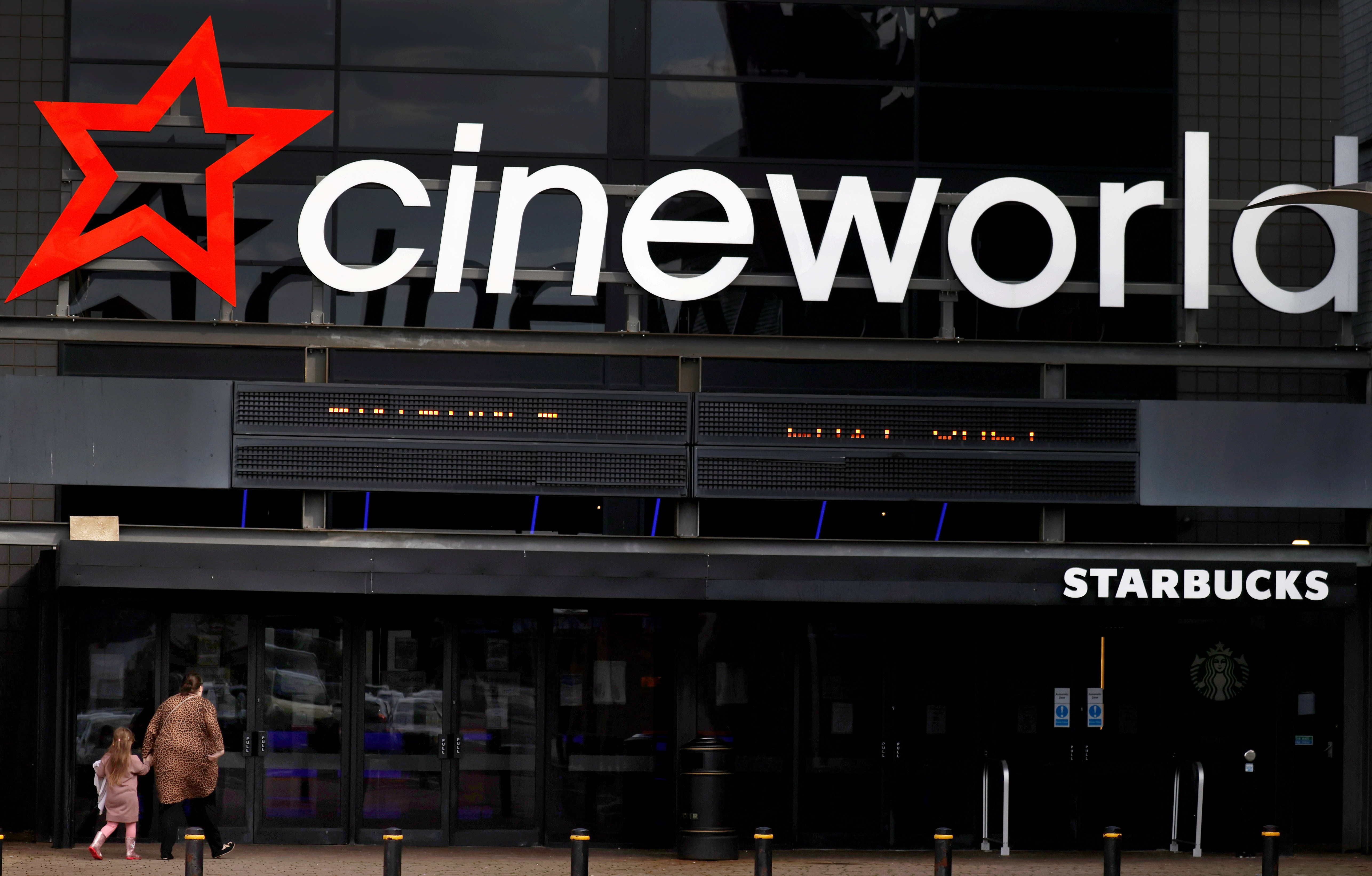 People enter a Cineworld cinema following the outbreak of the coronavirus disease near Manchester, Britain, October 4, 2020. REUTERS/Phil Noble