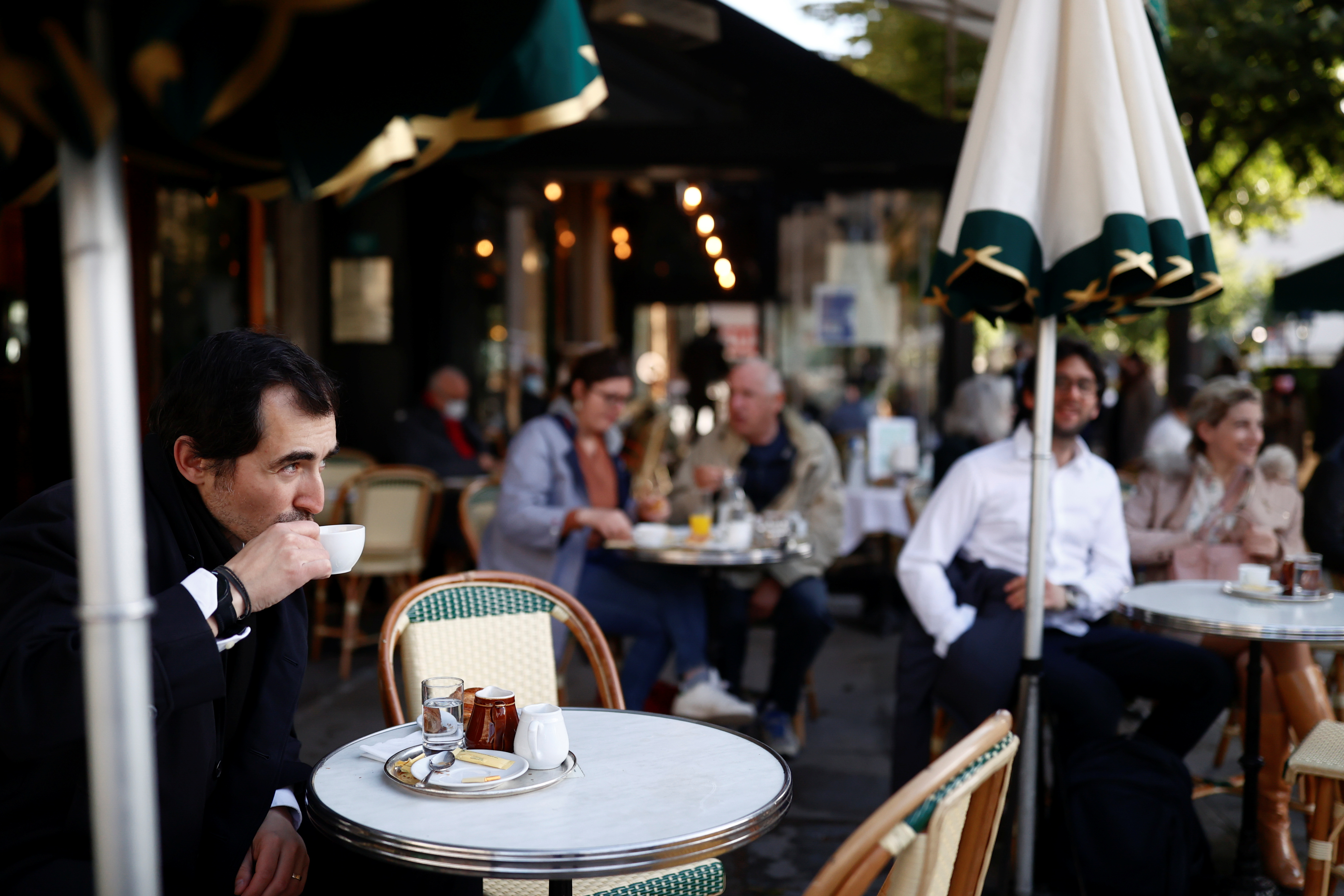 A customer enjoys a drink at the terrace of the cafe and restaurant Les Deux Magots, as cafes, bars and restaurants reopen their terraces after closing down for months, amid the coronavirus disease (COVID-19) outbreak, in Paris, France, May 19, 2021. REUTERS/Christian Hartmann