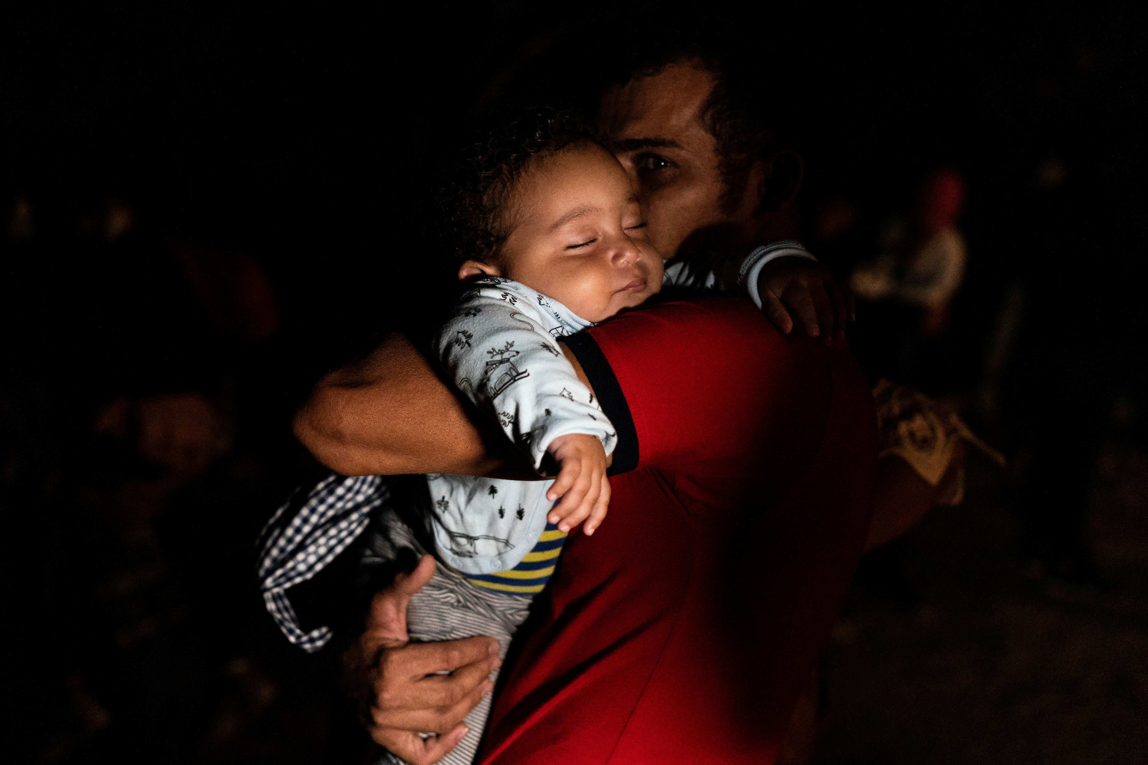 An asylum-seeking migrant father carries his child while waiting to be escorted by the U.S. Border Patrol after crossing the Rio Grande river into the United States from Mexico, in Roma, Texas, U.S., May 6, 2021. REUTERS/Go Nakamura/File Photo