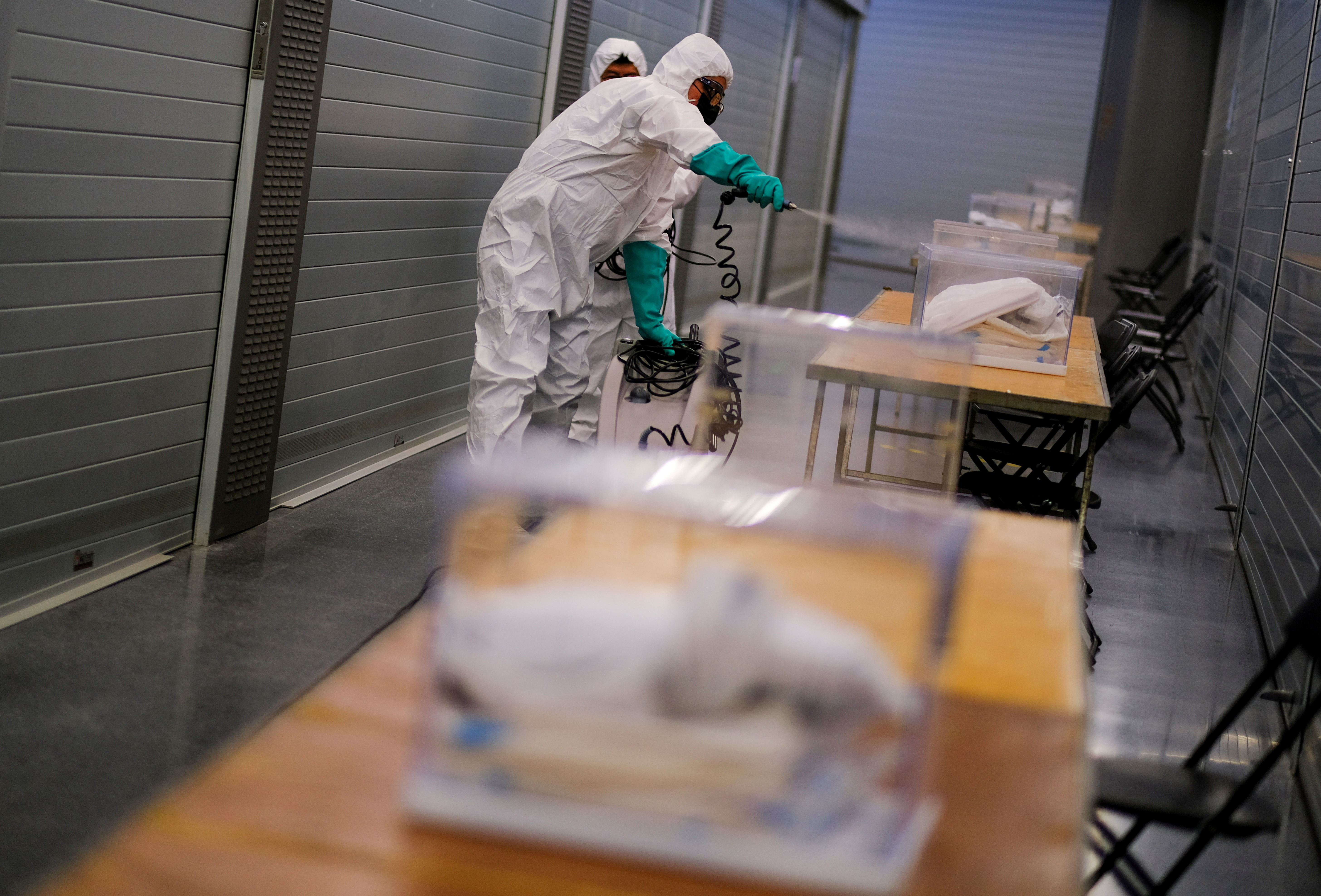 A worker uses disinfectant to clean ballot boxes containing personal protective equipment (PPE) supplies at Sant Antoni Market, which will be a polling station for the February 14th regional election, during the coronavirus disease (COVID-19) outbreak in Barcelona, Spain February 13, 2021.  REUTERS/Nacho Doce