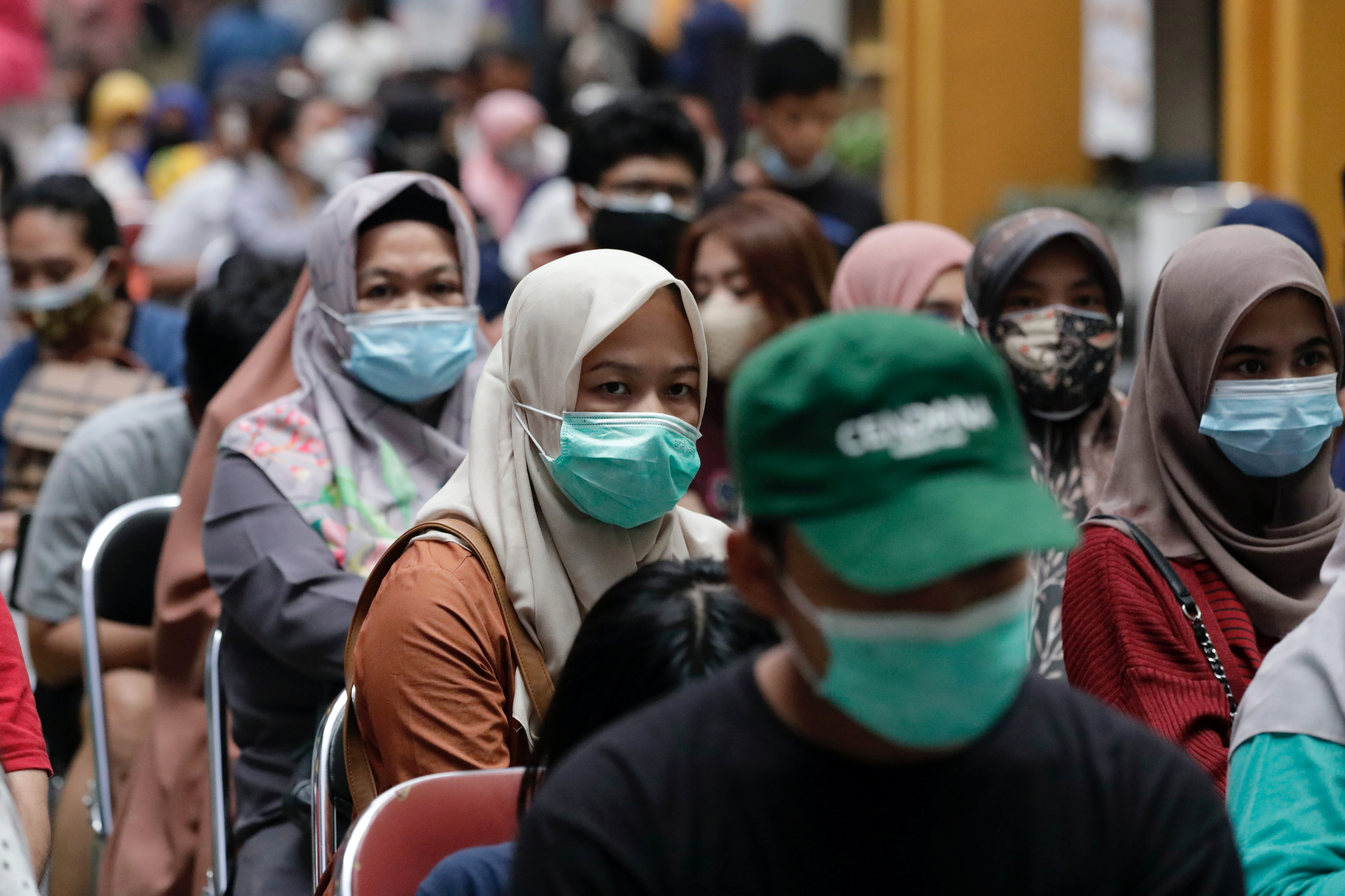 People wearing protective face masks queue up to receive a vaccine dose against the coronavirus disease (COVID-19)  during a mass vaccination program at a shopping mall in Jakarta, Indonesia, August 31, 2021. REUTERS/Ajeng Dinar Ulfiana