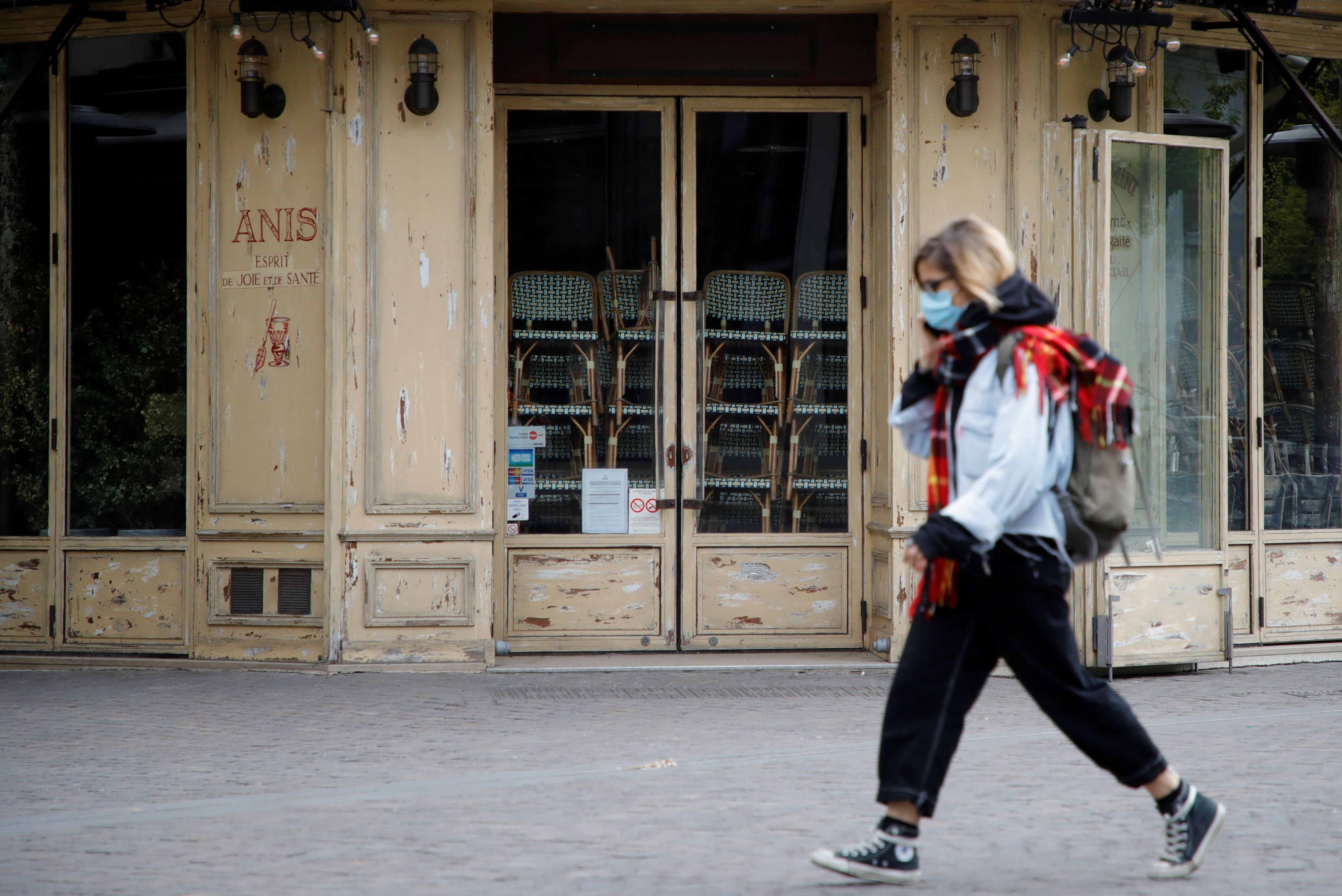 A woman, wearing a protective face mask, walks past a closed restaurant in Paris amid the coronavirus disease (COVID-19) outbreak in Paris, France, April 29, 2021. REUTERS/Sarah Meyssonnier