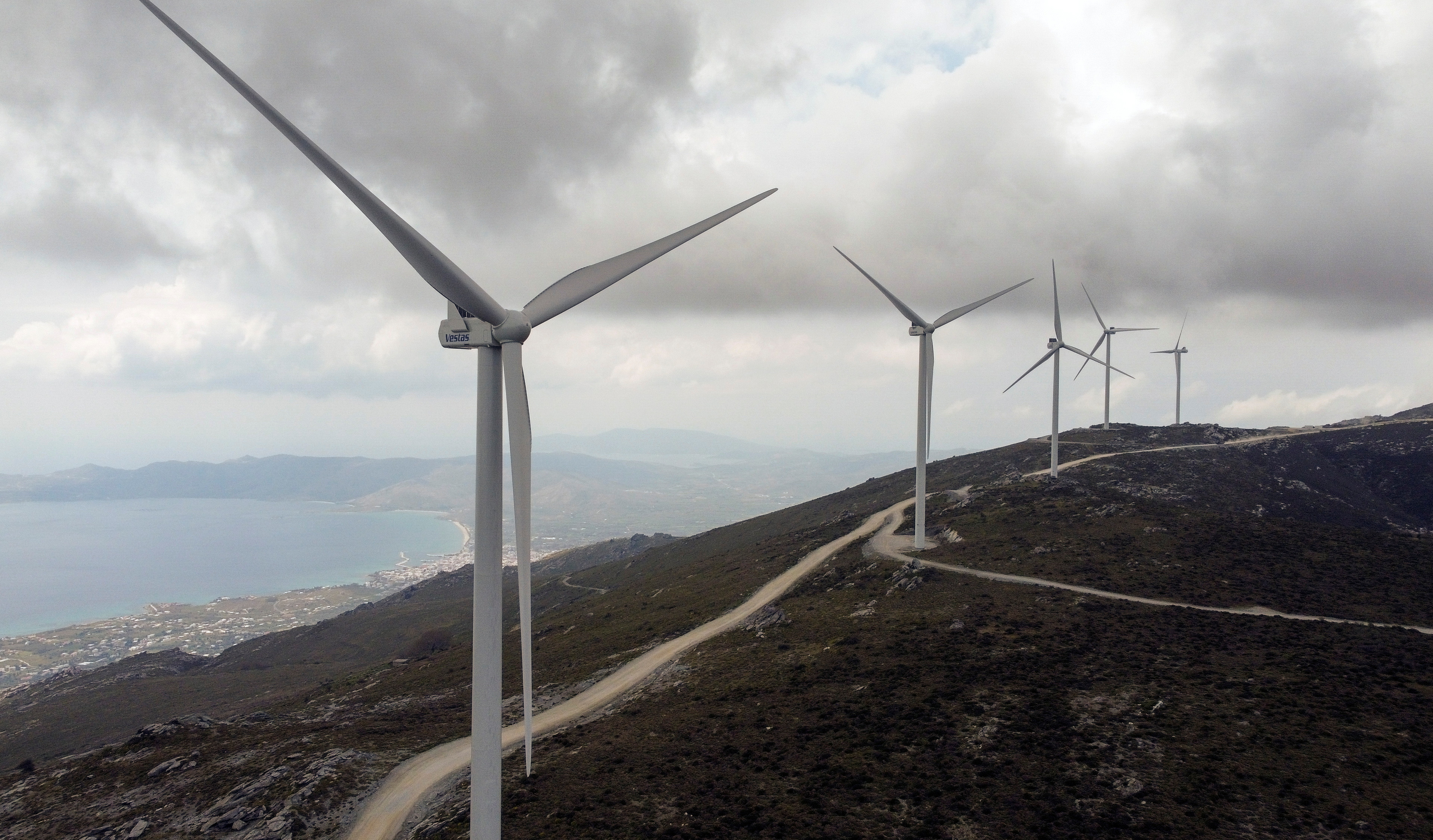 Wind turbines are seen on a mountain as the town of Karystos is seen in the background, on the island of Evia, Greece, April 16, 2021. Picture taken April 16, 2021. Picture taken with a drone. REUTERS/Alkis Konstantinidis