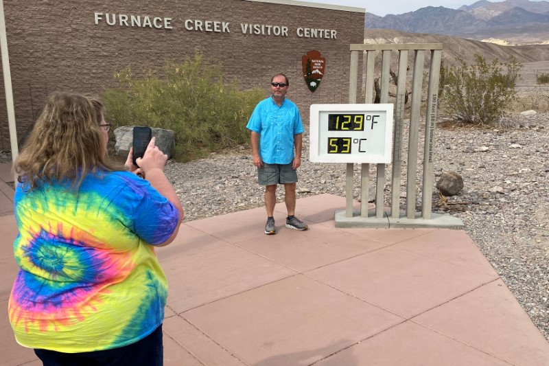 Patrick Fox, 63, from Utah poses for a picture next to the thermometer at the Furnace Creek Visitor Center at Death Valley National Park, with the temperature showing at 129 degrees Fahrenheit (53.8 C) in Death Valley, California, U.S. June 16, 2021. Picture taken June 16, 2021.  REUTERS/Norma Galeana