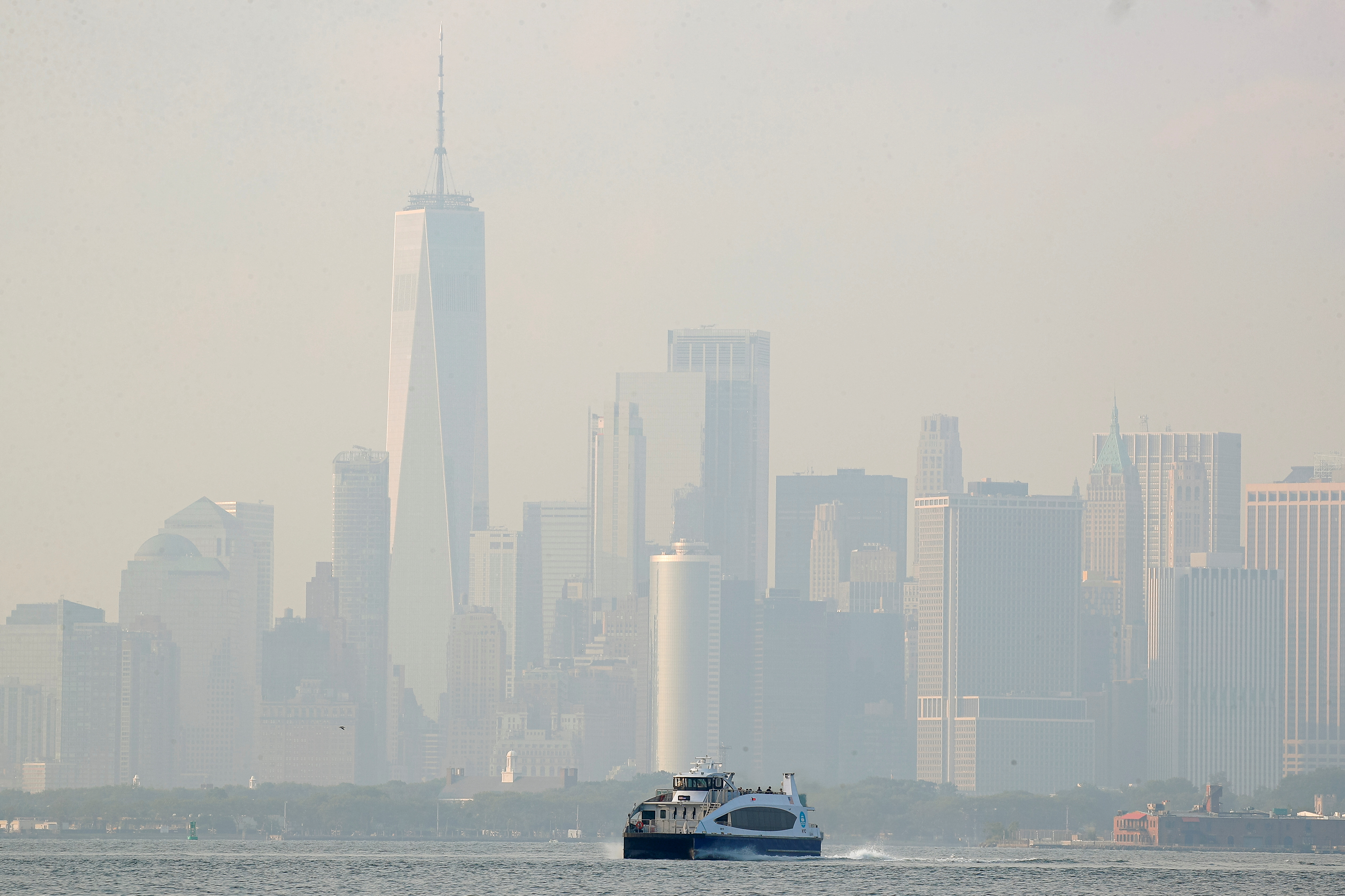 The lower Manhattan skyline is seen through a cover of wildfire smoke as a NYC Ferry makes its way through the Upper Bay as seen from Brooklyn, New York, U.S., July 21, 2021.  REUTERS/Brendan McDermid