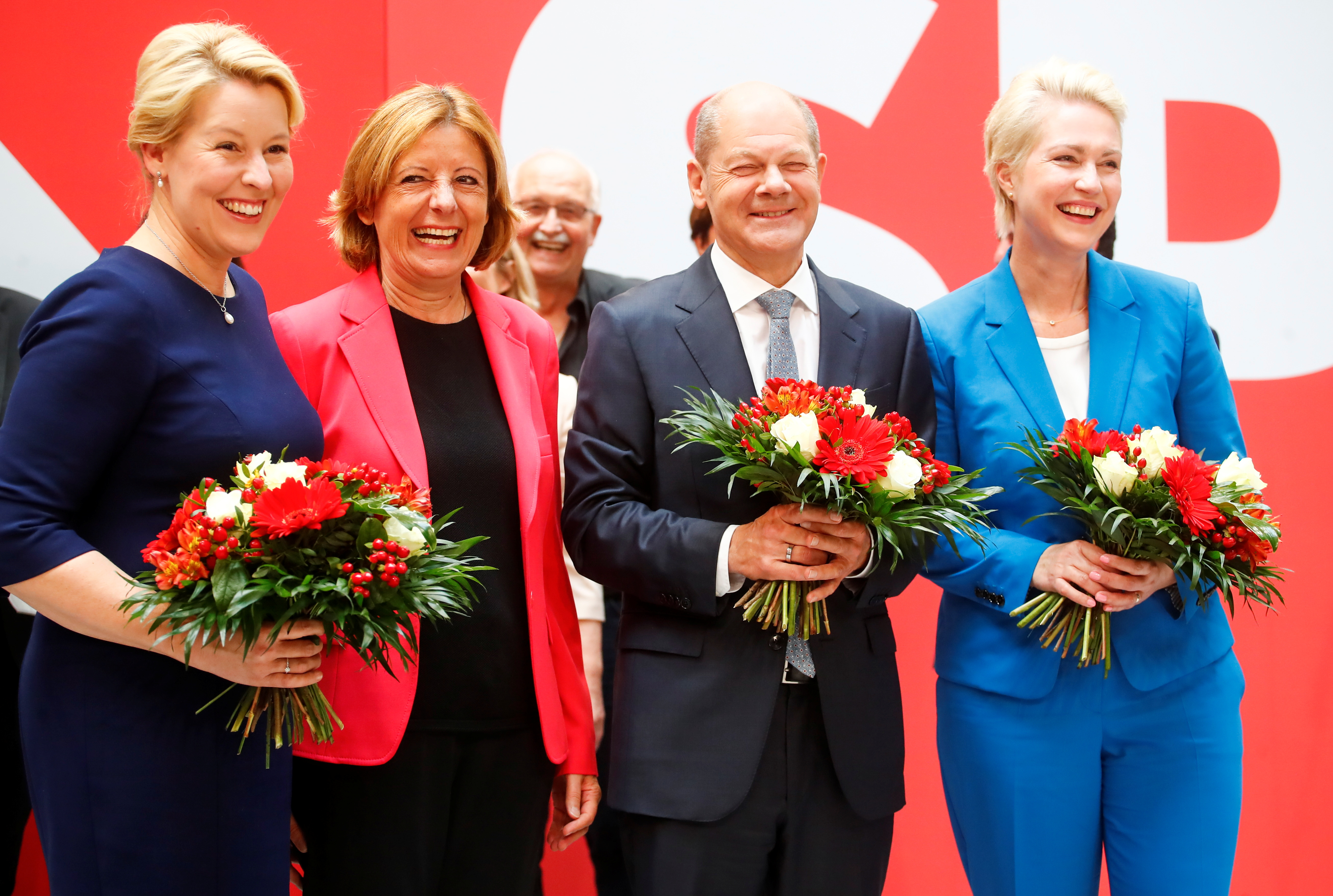 Social Democratic Party (SPD) leader and top candidate for chancellor Olaf Scholz, Mecklenburg-Western Pomerania state Prime Minister Manuela Schwesig, Rhineland-Palatinate State Premier Malu Dreyer and SPD member Franziska Giffey carry bouquets of flowers at their party leadership meeting, one day after the German general elections, in Berlin, Germany, September 27, 2021. REUTERS/Wolfgang Rattay