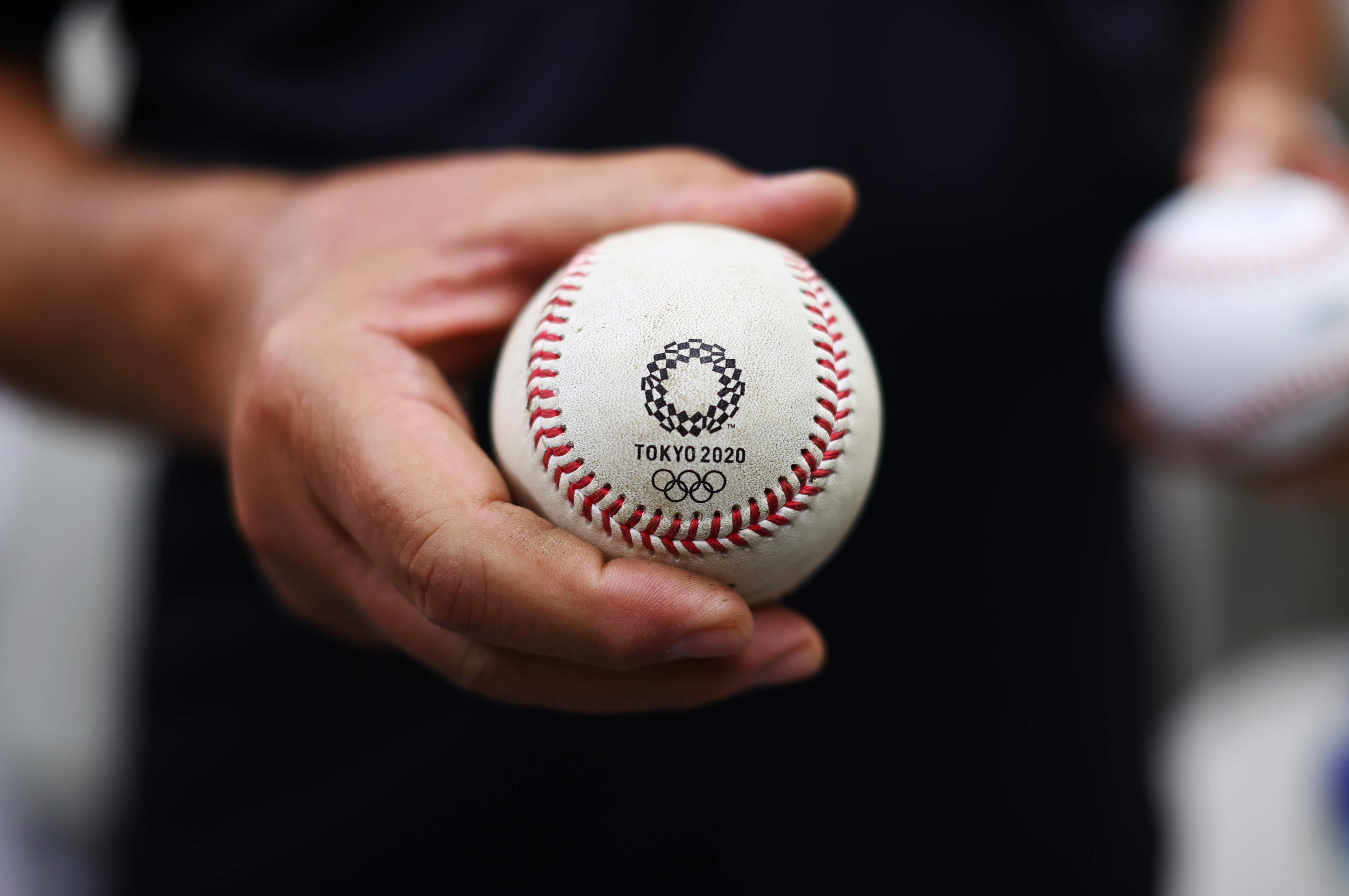 Umpiring officials display a baseball as they rub baseballs with mud prior to a game during the Tokyo 2020 Olympics at the Yokohama Baseball Stadium in Yokohama, Japan July 30, 2021. REUTERS/Jorge Silva
