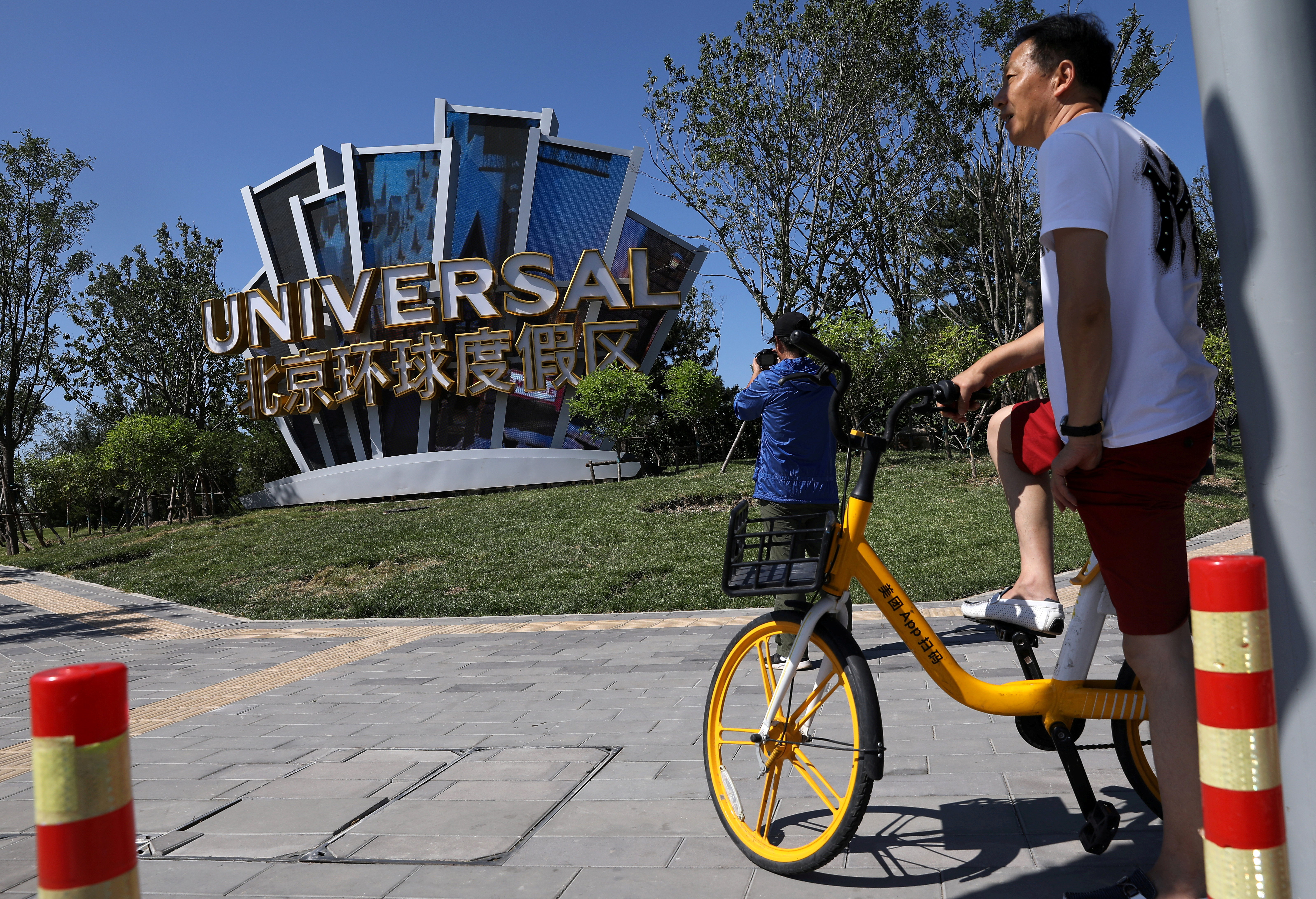 A man rides a bike of a bike-sharing service near a giant sign Universal Beijing Resort, ahead of its opening, in Beijing, China August 27, 2021. REUTERS/Tingshu Wang/File Photo