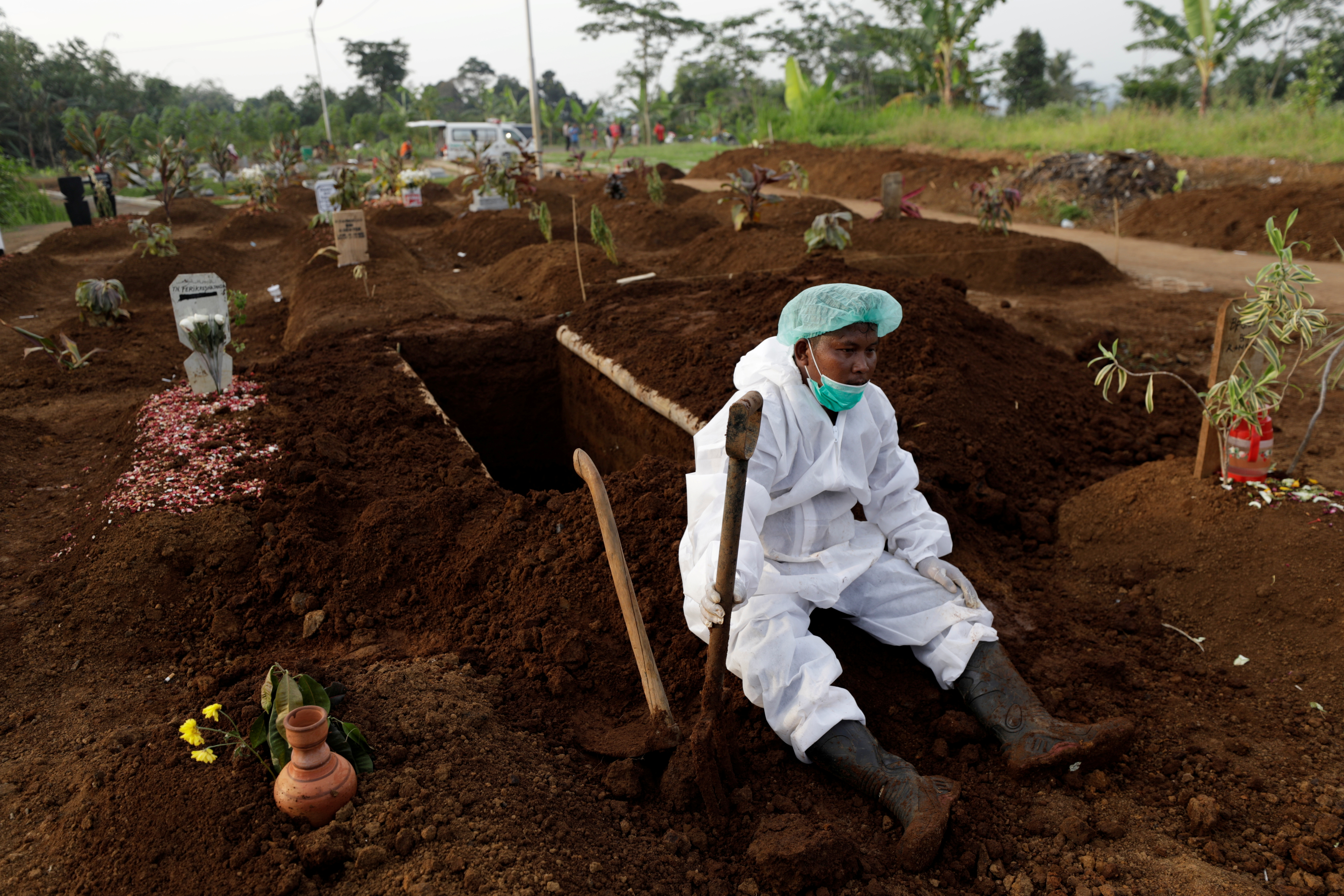 A gravedigger wearing personal protective equipment rests after the burial of 64-year-old Yoyoh Sa'diah who passed away due to complications related to COVID-19 whilst isolating at her home in Bogor, West Java province, Indonesia, July 8, 2021. REUTERS/Willy Kurniawan/File Photo