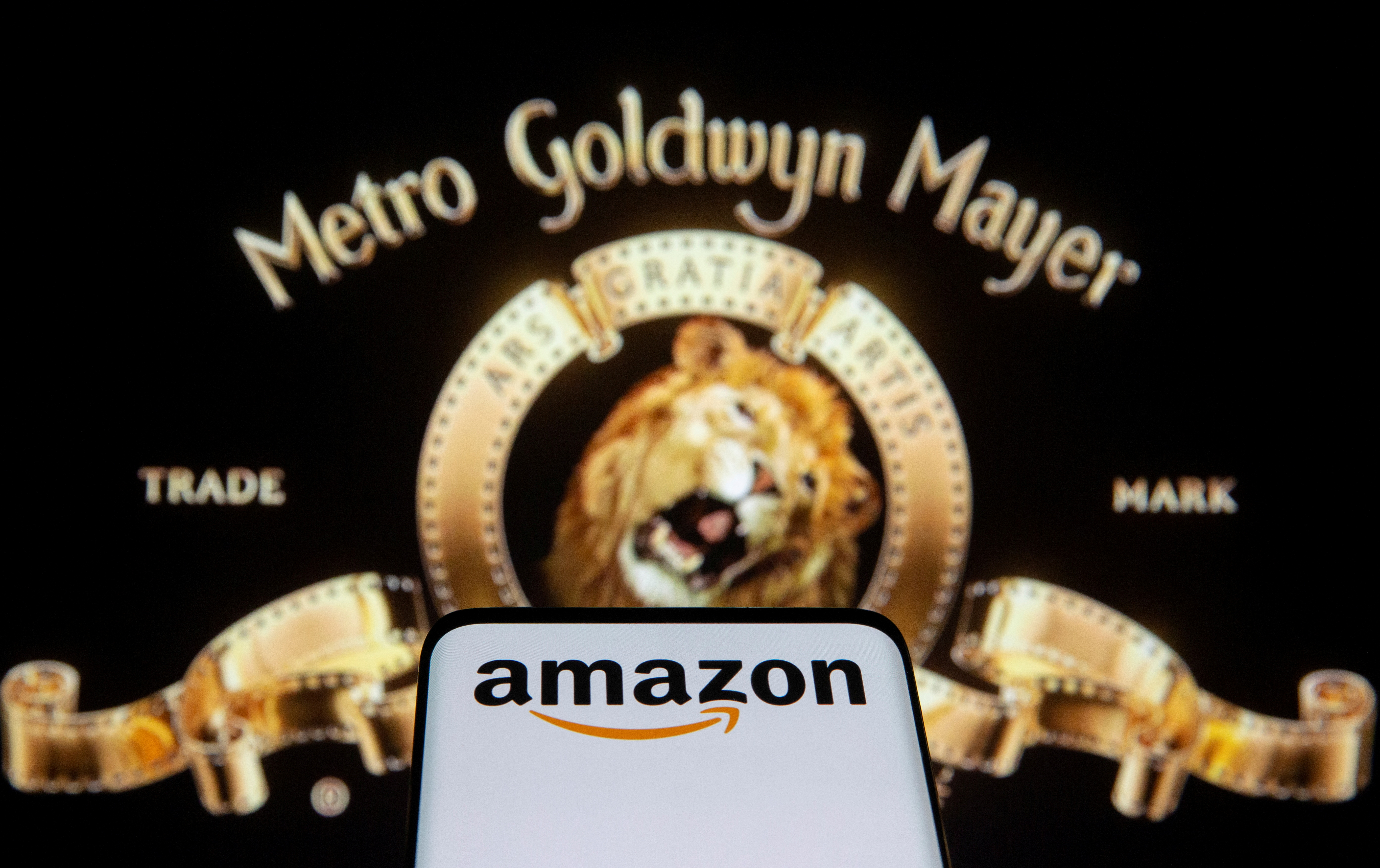 Smartphone with Amazon logo is seen in front of displayed MGM logo in this illustration taken, May 26, 2021. REUTERS/Dado Ruvic/Illustration