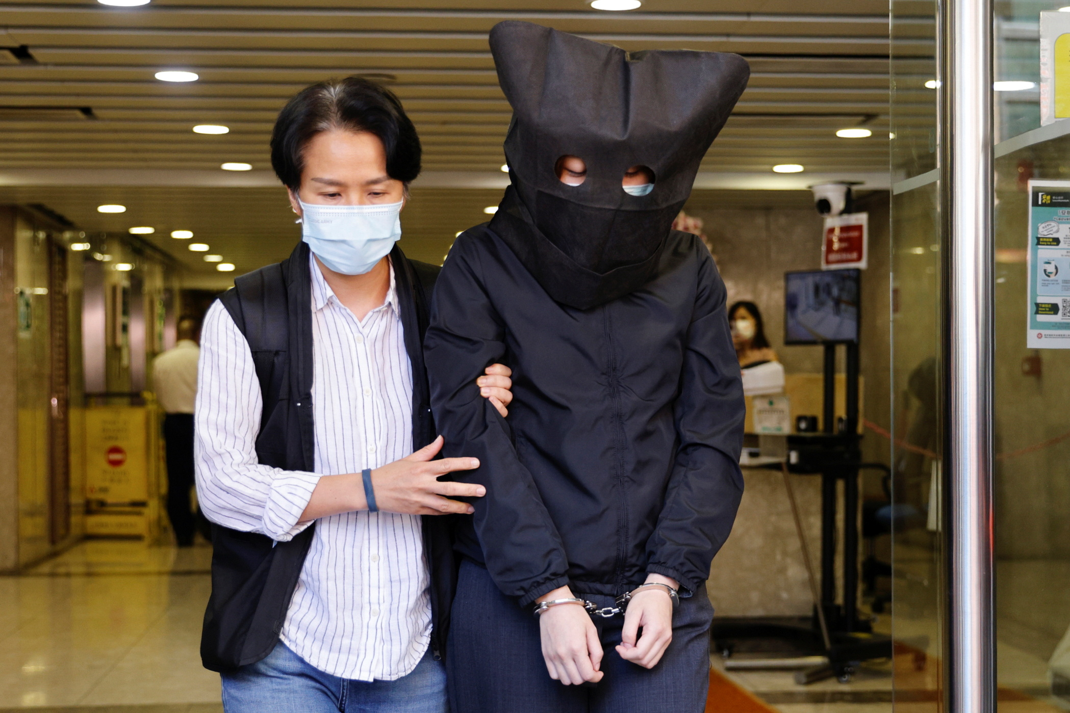 A police officer escorts one of five suspects, detained on suspicion of publishing and distributing seditious material, in Hong Kong, China July 22, 2021. REUTERS/Tyrone Siu
