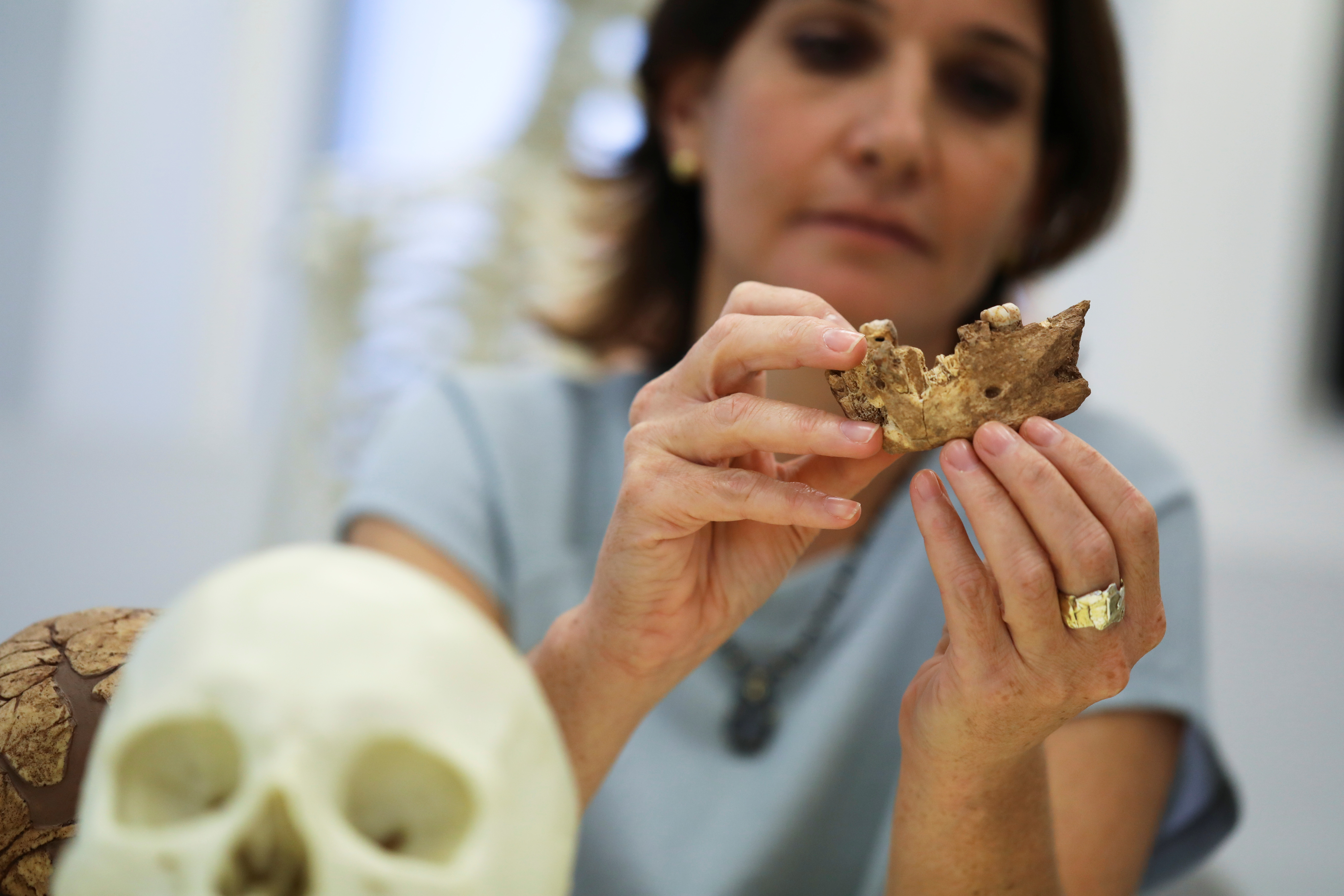 Hila May, a physical anthropologist at the Dan David Center and the Shmunis Institute of Tel Aviv University holds what scientists say is a piece of fossilised bone of a previously unknown kind of early human discovered at the Nesher Ramla site in central Israel, during an interview with Reuters at The Steinhardt Museum of Natural History in Tel Aviv, Israel June 23, 2021. Picture taken June 23, 2021. REUTERS/Ammar Awad