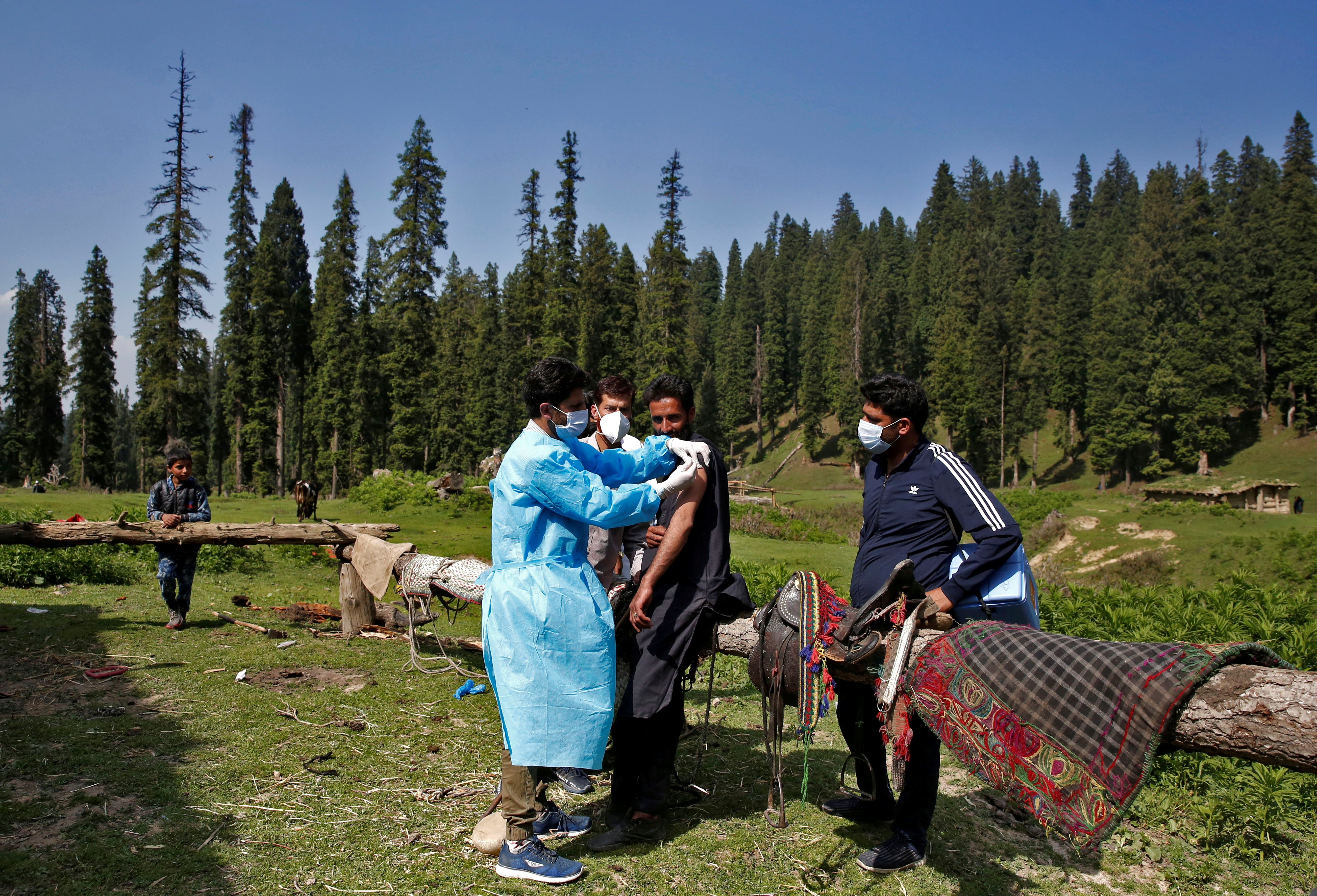 A healthcare worker gives a dose of COVISHIELD, a coronavirus disease (COVID-19) vaccine manufactured by Serum Institute of India, to a shepherd man during a vaccination drive at a forest area in south Kashmir's Pulwama district June 7, 2021. REUTERS/Danish Ismail/File Photo