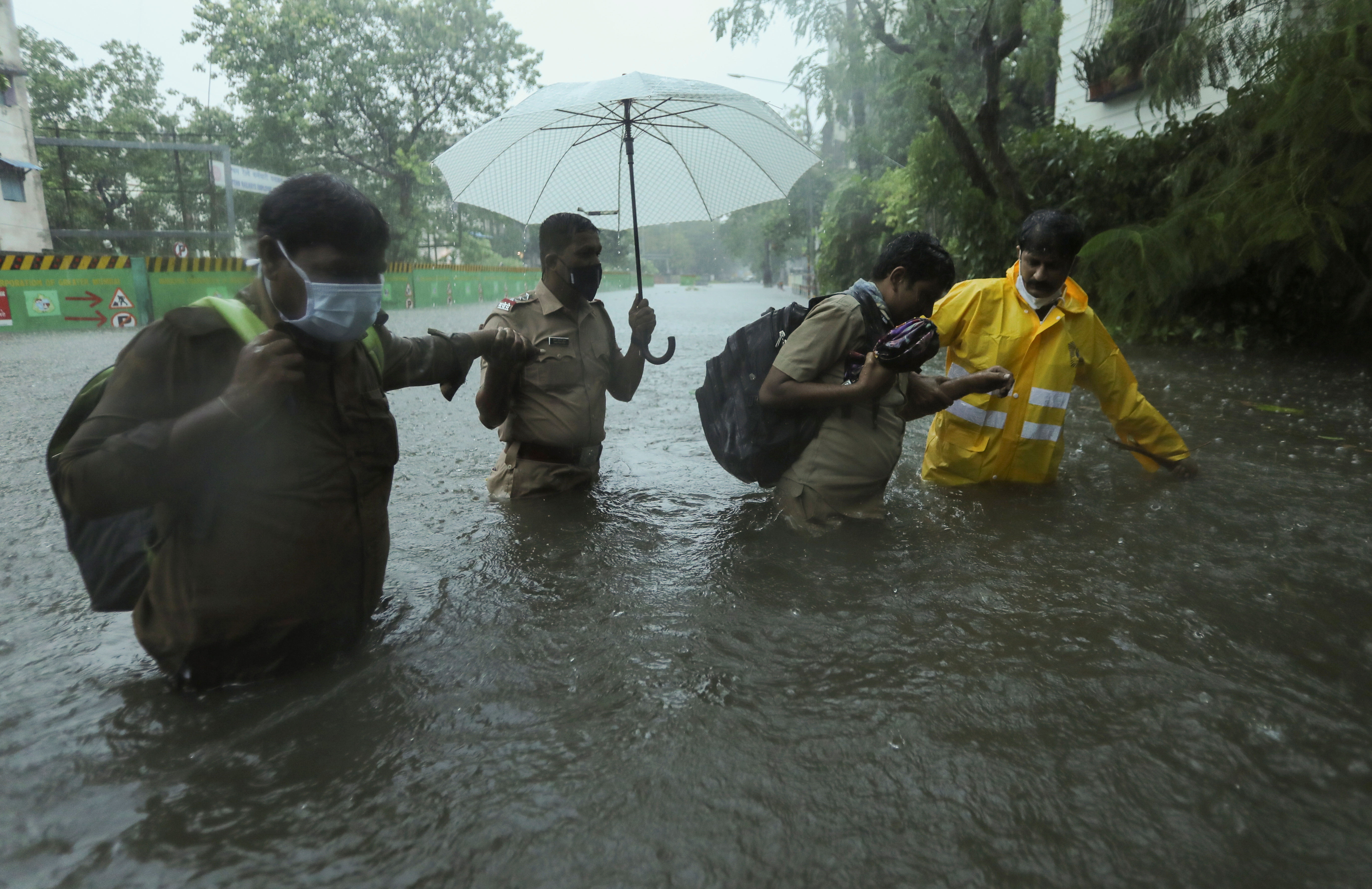 Frontline workers help people cross a flooded street after heavy rainfall caused by Cyclone Tauktae in Mumbai, India, May 17, 2021. REUTERS/Francis Mascarenhas