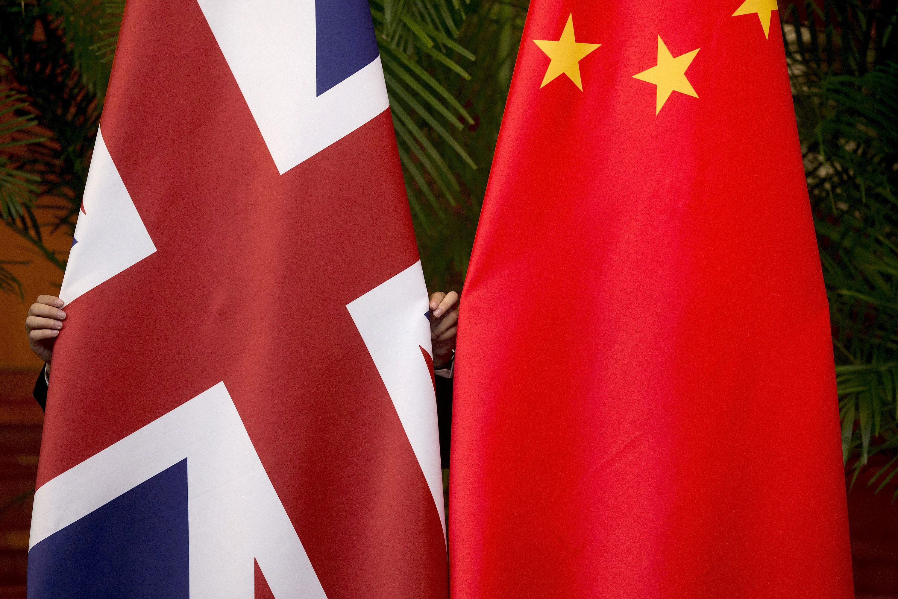 A worker adjusts British and China (R) national flags on display for a signing ceremony at the seventh UK-China Economic and Financial Dialogue