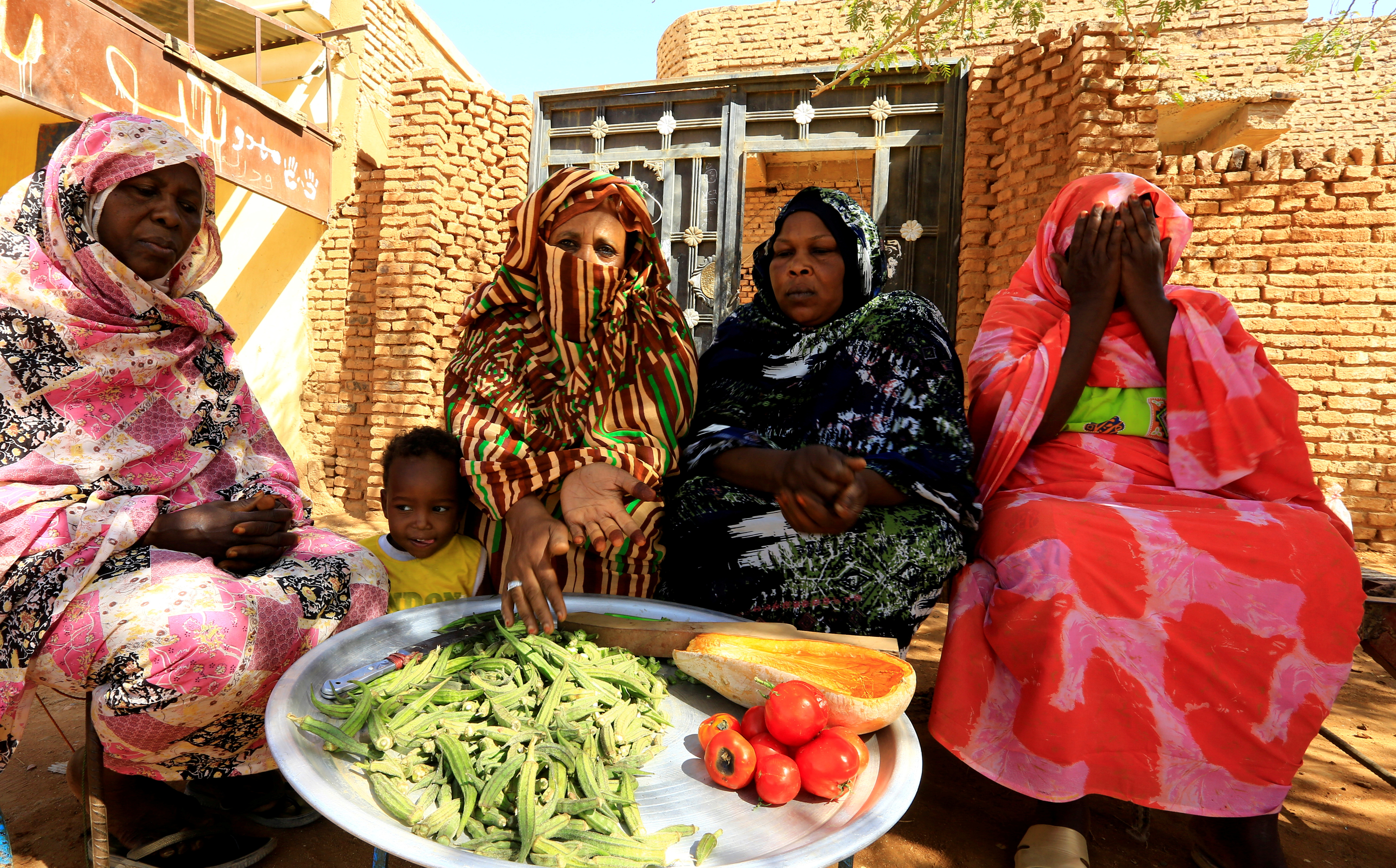 Women sit together as they prepare food for their families in Khartoum north, Sudan,March 2, 2021.  REUTERS/Mohamed Nureldin Abdallah/File Photo