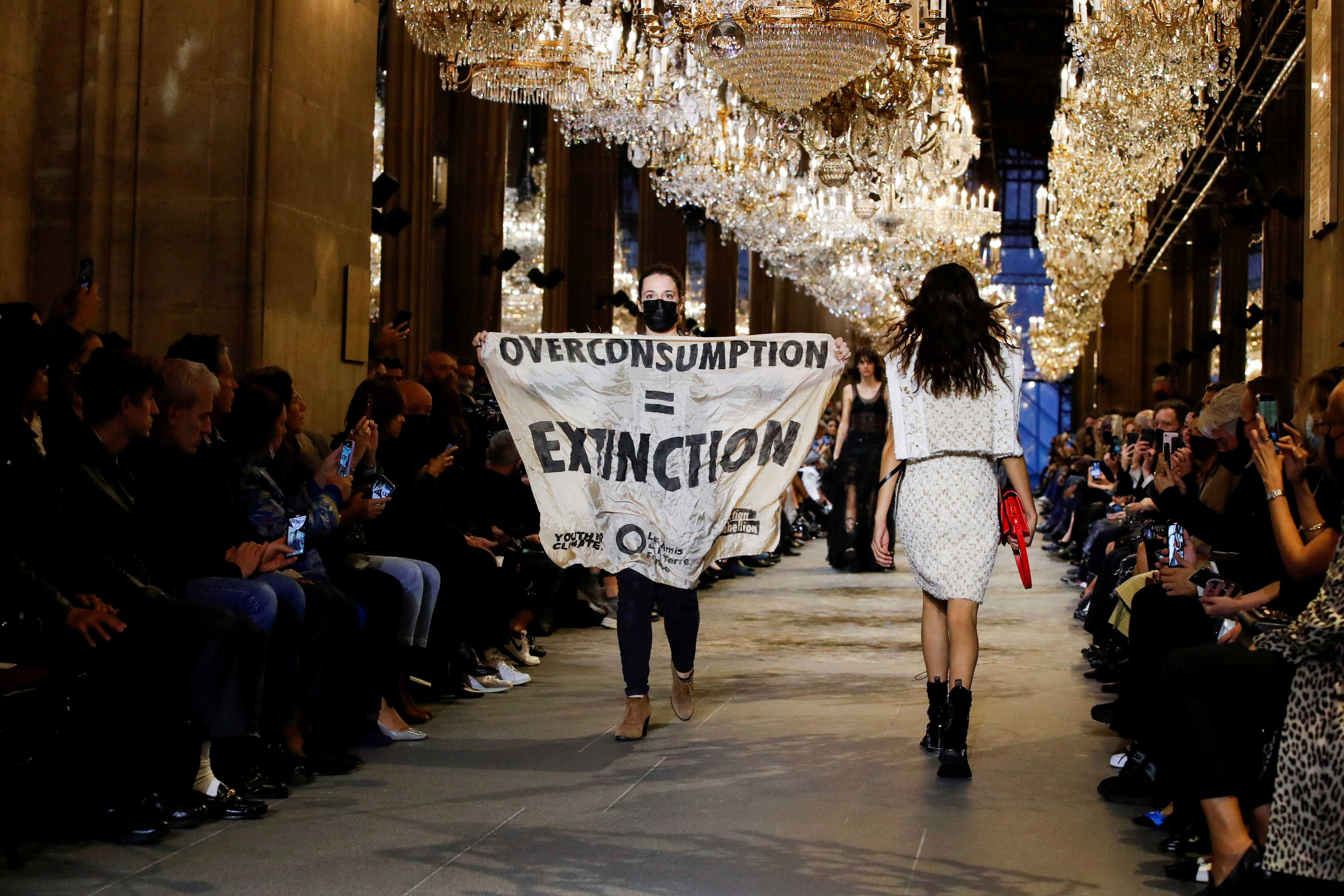 """An activist walks on the ramp with a banner that says """"Overconsumption = Extinction"""" as she crashes the designer Nicolas Ghesquiere Spring/Summer 2022 women's ready-to-wear collection show for fashion house Louis Vuitton during Paris Fashion Week in Paris, France, October 5, 2021. REUTERS/Gonzalo Fuentes"""