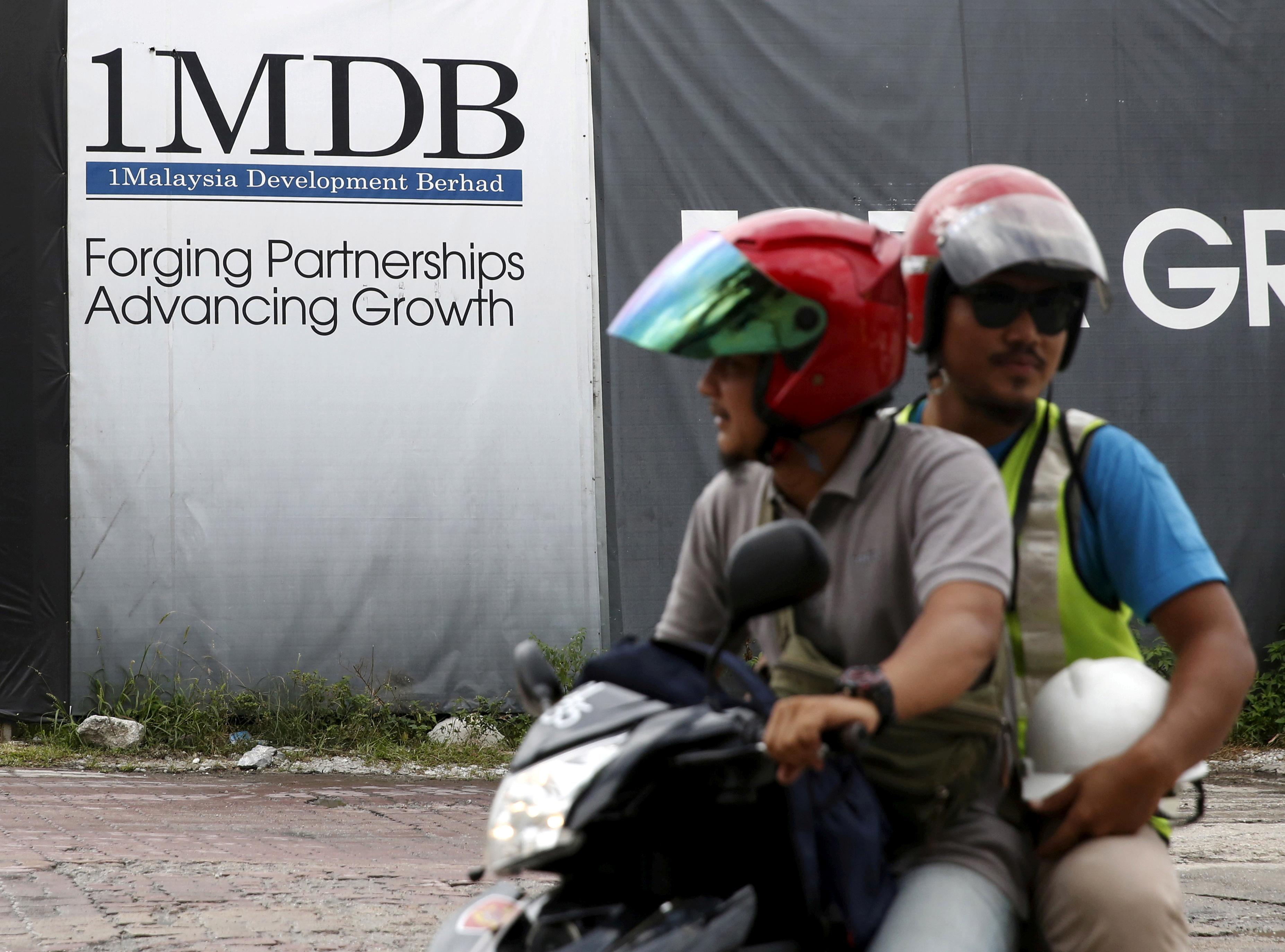 Motorcyclists pass a 1Malaysia Development Berhad (1MDB) billboard at the Tun Razak Exchange development in Kuala Lumpur, Malaysia, February 3, 2016. REUTERS/Olivia Harris