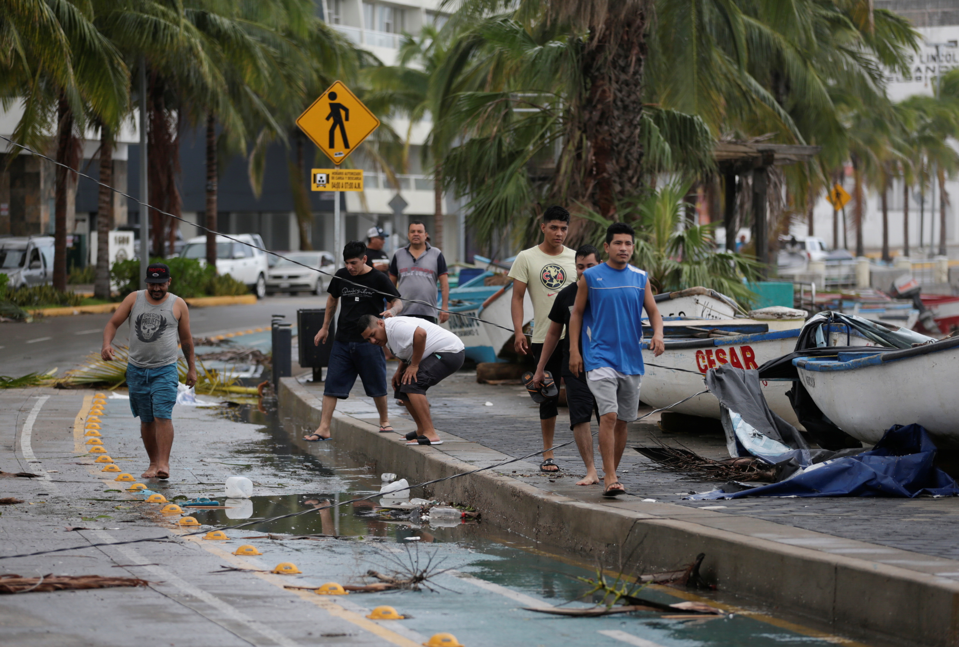 People walk along a street as hurricane Pamela pounds the Pacific coast resort with strong winds as it makes landfall in Mazatlan, Mexico October 13, 2021. REUTERS/Daniel Becerril