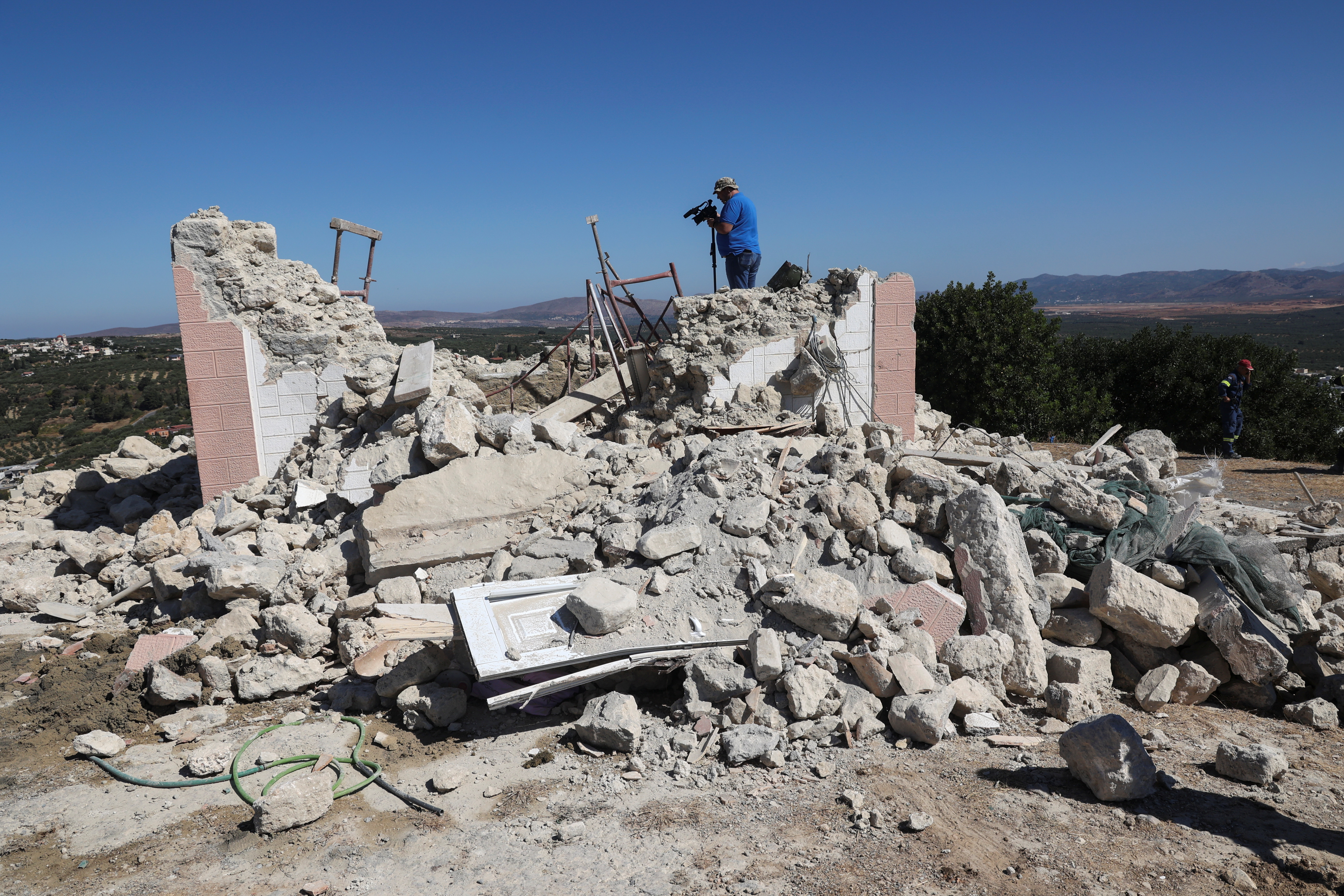 A camera operator films amid the rubble of a demolished church following an earthquake, in the town of Arkalochori on the island of Crete, Greece, September 27, 2021. REUTERS/Stefanos Rapanis