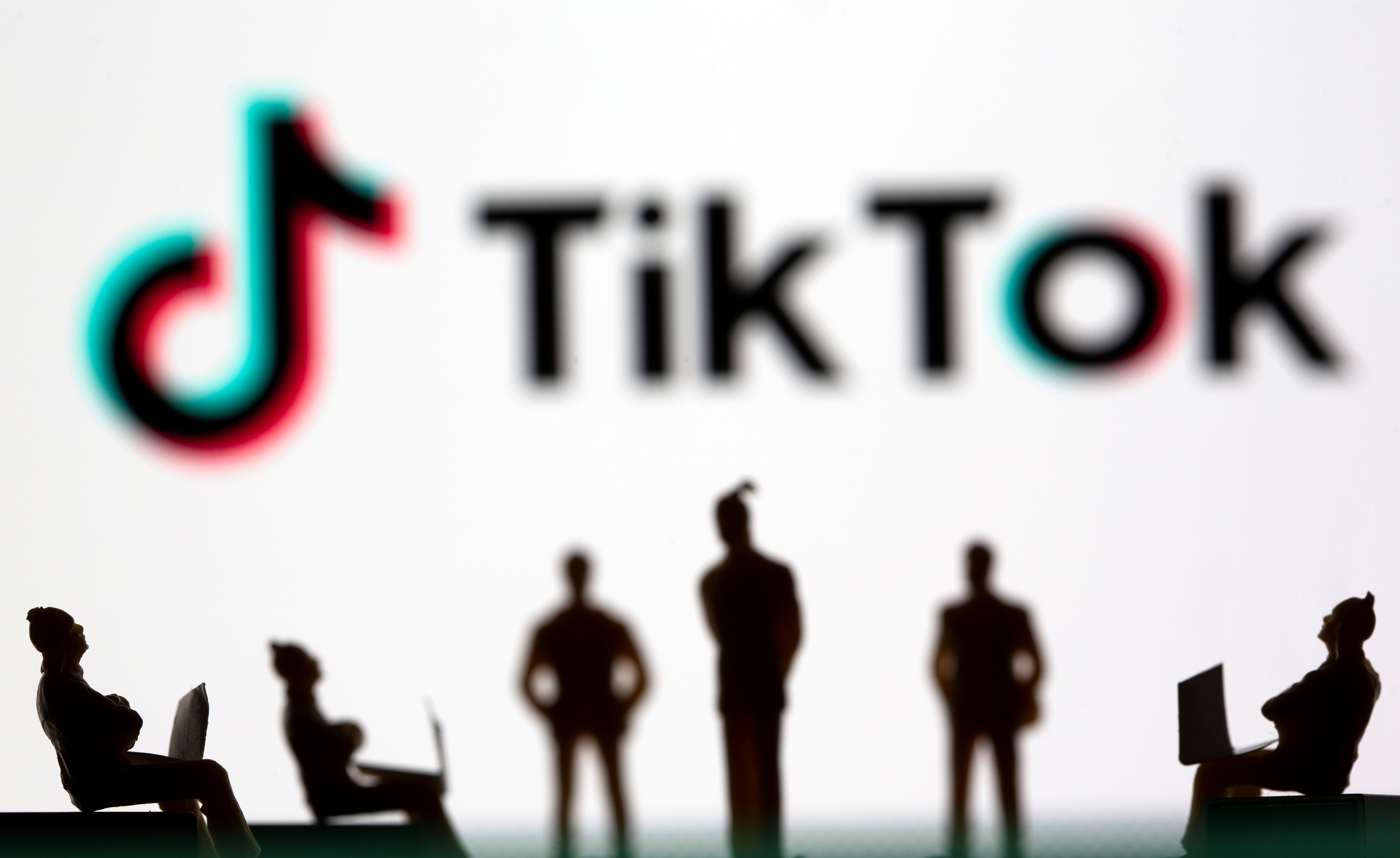 Small toy figures are seen in front of TikTok logo in this illustration picture taken March 15, 2021. REUTERS/Dado Ruvic/File Photo