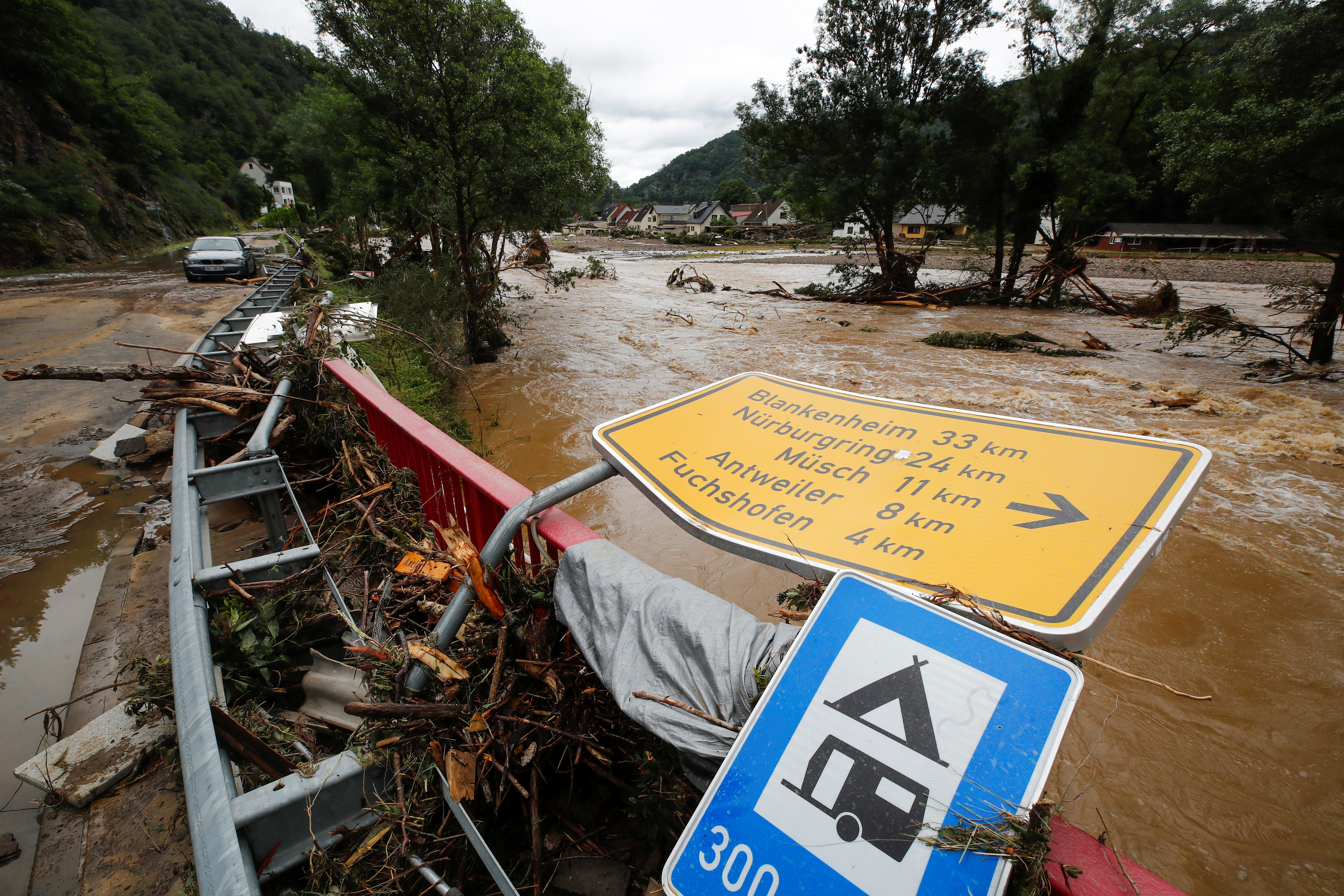 A collapsed sign is seen next to a river at a flood-affected area, following heavy rainfalls, in Schuld, Germany, July 15, 2021. REUTERS/Wolfgang Rattay