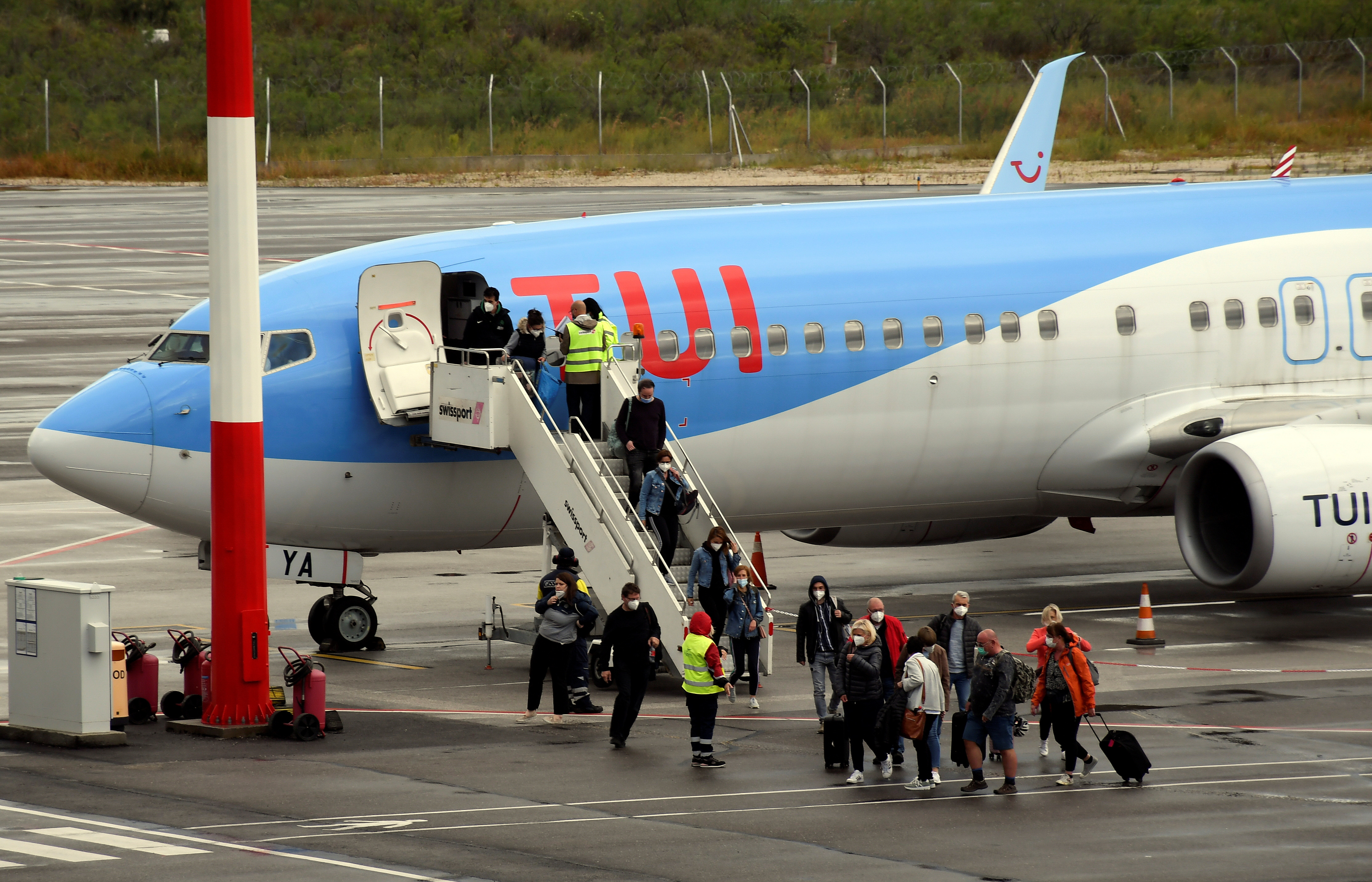 Passengers of TUI Airways flight from Dusseldorf arrive at Ioannis Kapodistrias International Airport, as the country's tourism season officially opens, on the island of Corfu, Greece, May 15, 2021. REUTERS/Adonis Skordilis