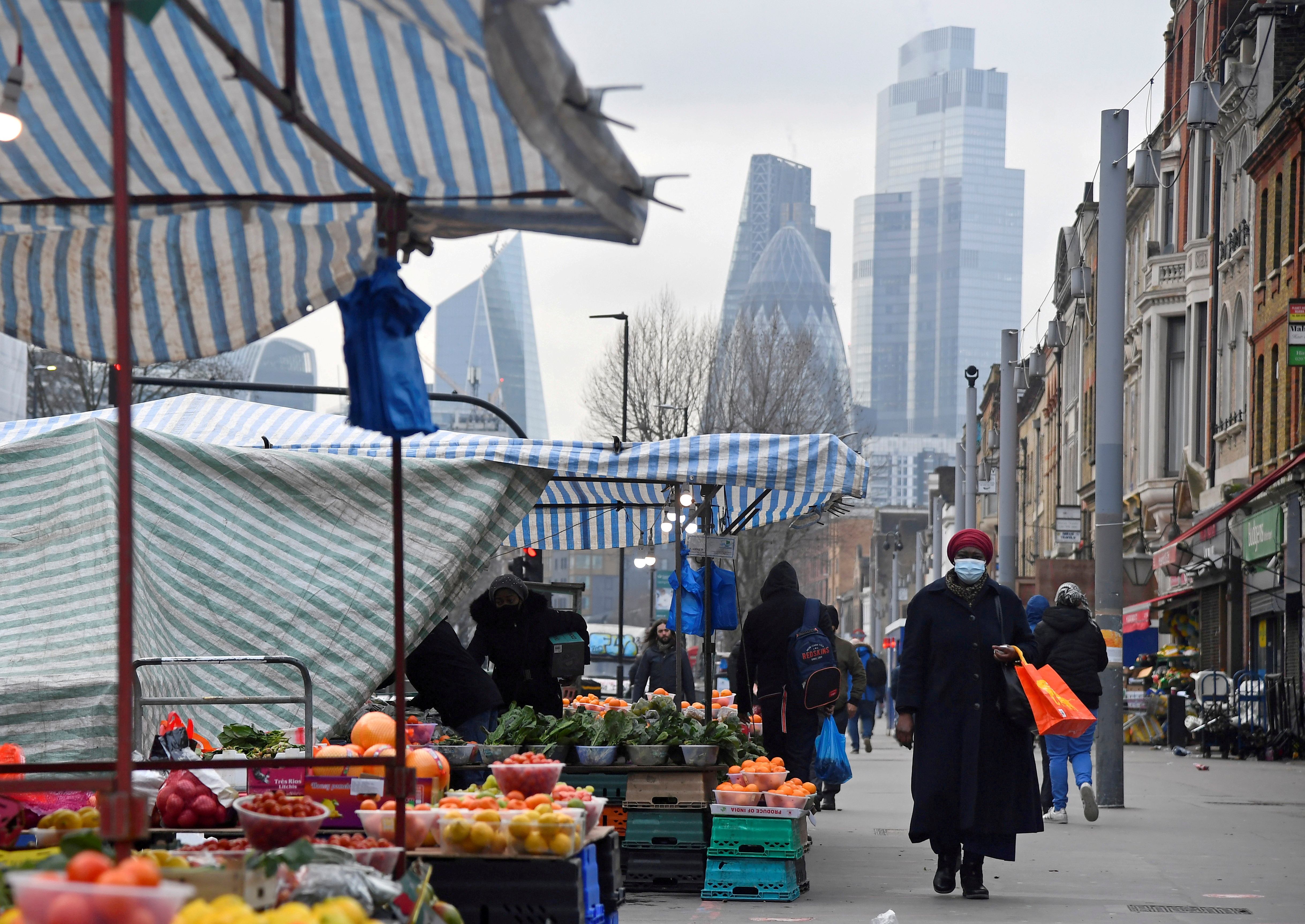 People shop at market stalls, with skyscrapers of the CIty of London financial district seen behind, amid the coronavirus disease (COVID-19) pandemic, in London, Britain, January 15, 2021. REUTERS/Toby Melville/Files