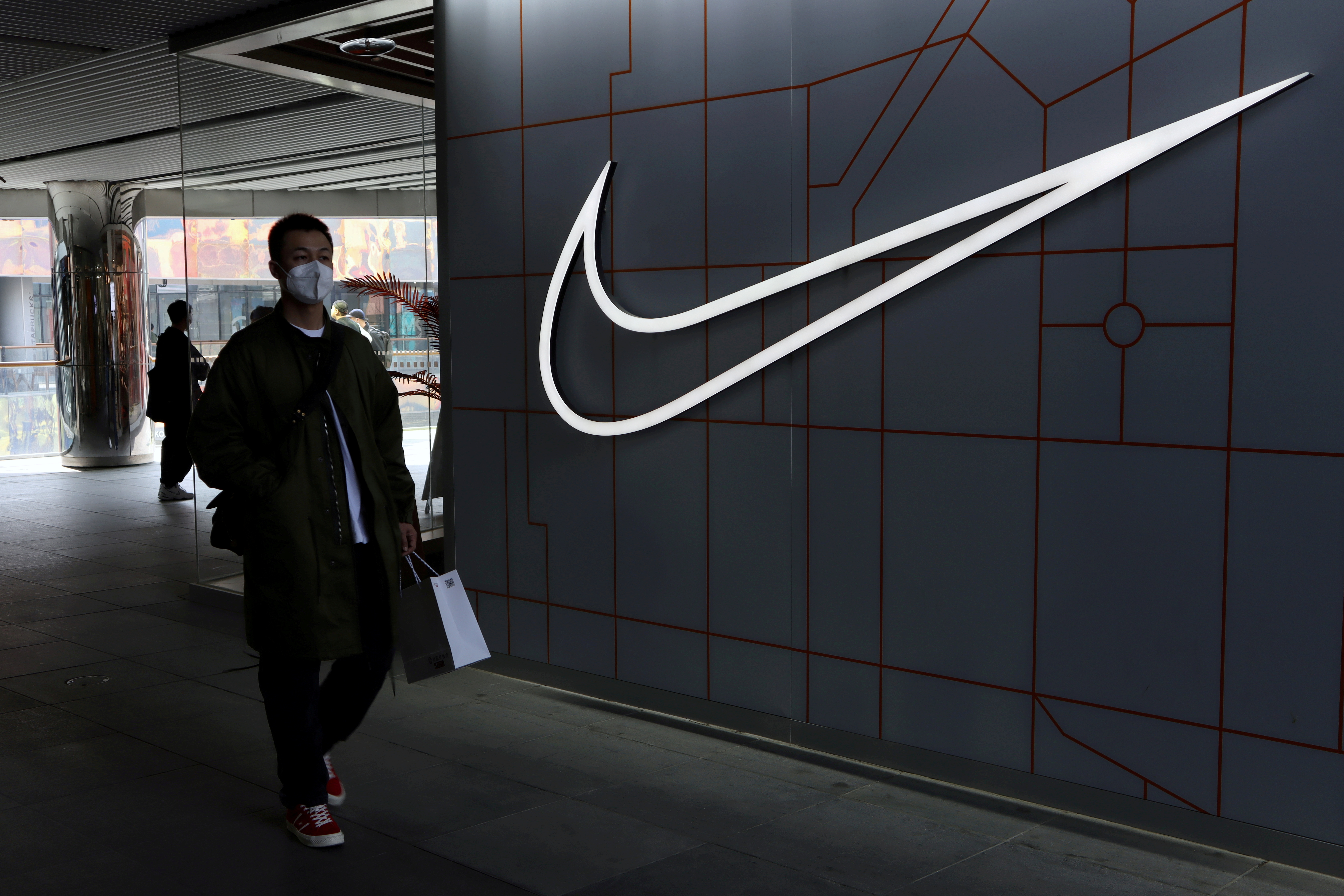 A man walks past a store of the sporting goods retailer Nike Inc at a shopping complex in Beijing, China March 25, 2021. REUTERS/Florence Lo/File Photo