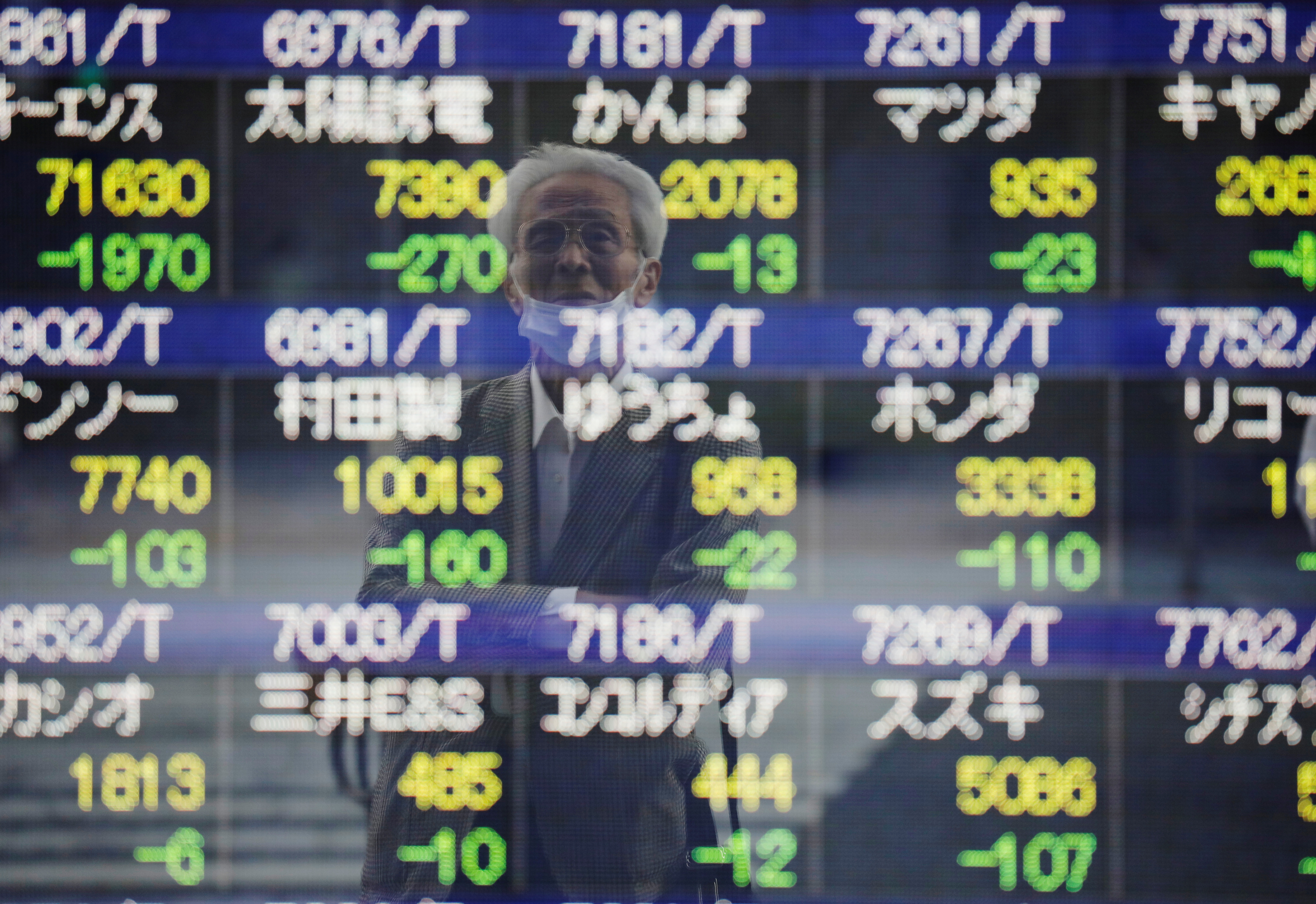 A man wearing a protective mask, amid the COVID-19 outbreak, is reflected on an electronic board displaying stock prices outside a brokerage in Tokyo, Japan, September 21, 2021. REUTERS/Kim Kyung-Hoon