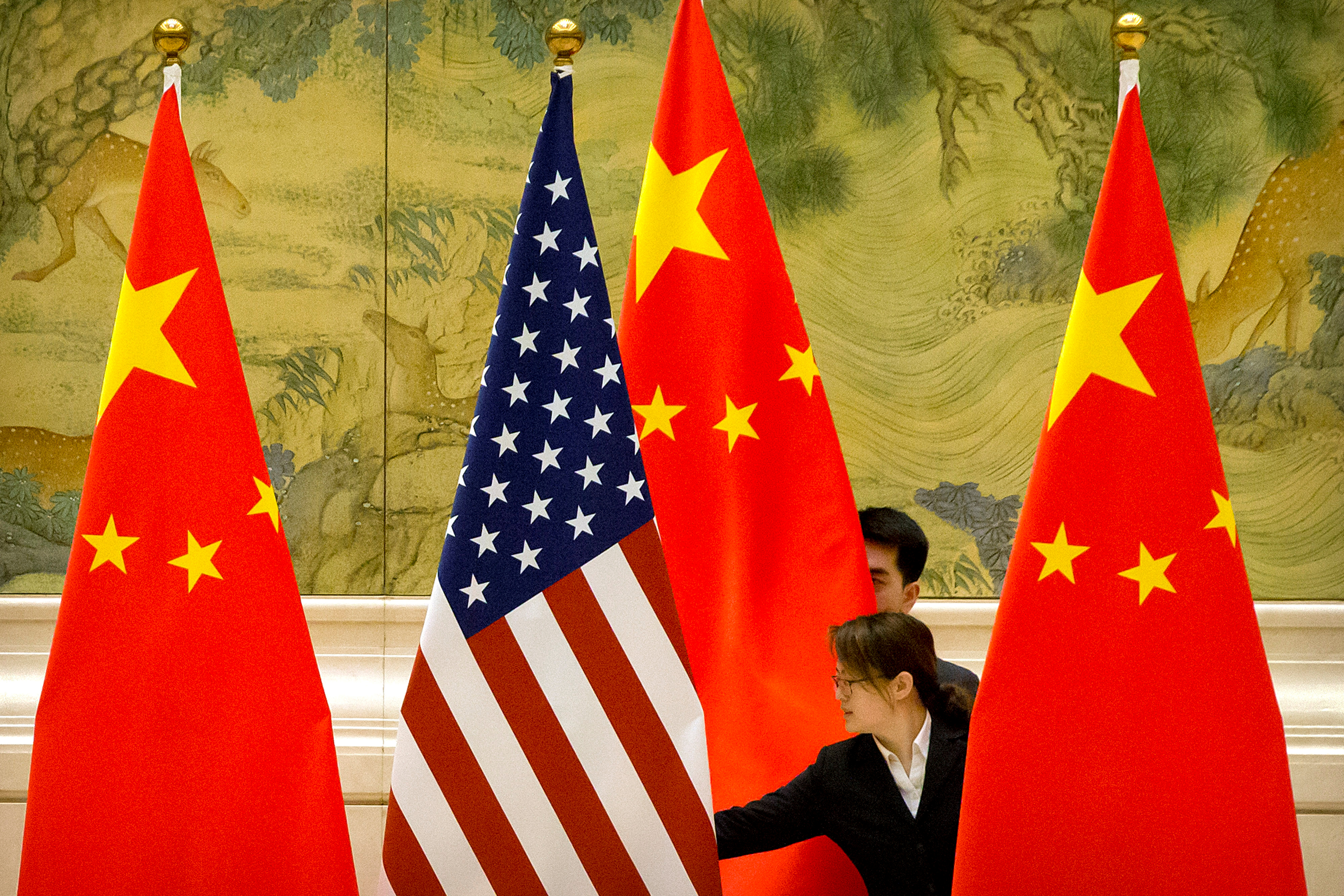 Chinese staffers adjust U.S. and Chinese flags before the opening session of Sino-U.S. trade negotiations in Beijing, Feb. 14, 2019. Mark Schiefelbein/Pool via REUTERS/File Photo
