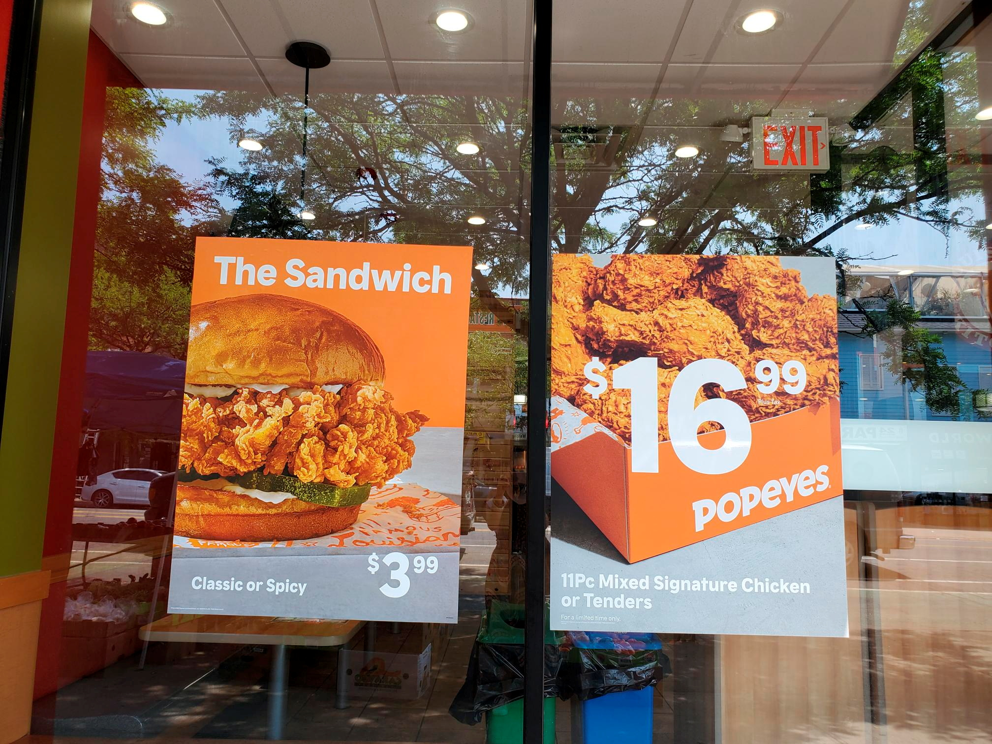 Signs advertising a box of fried chicken for $16.99 and a sandwich are seen at a Popeyes restaurant in New York City, New York, U.S. May 26, 2021. Picture taken May 26, 2021. REUTERS/Hilary Russ