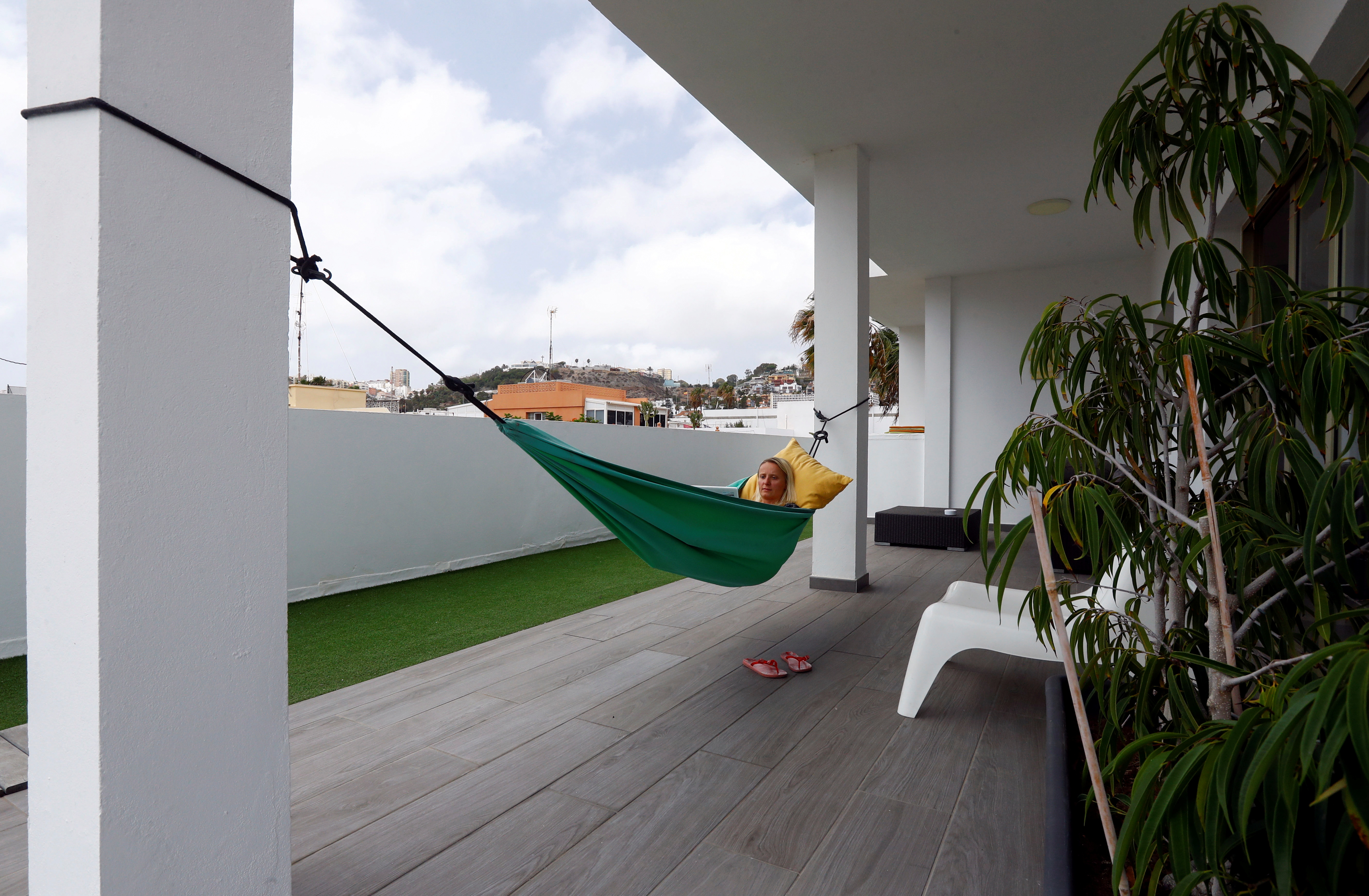 Olga Paul, a 34-year-old from Germany works remotely from Las Palmas De Gran Canaria, relaxes in hammock, amid the coronavirus disease (COVID-19) outbreak, in Gran Canaria, Spain July 23, 2021.  Picture taken July 23, 2021. REUTERS/Borja Suarez
