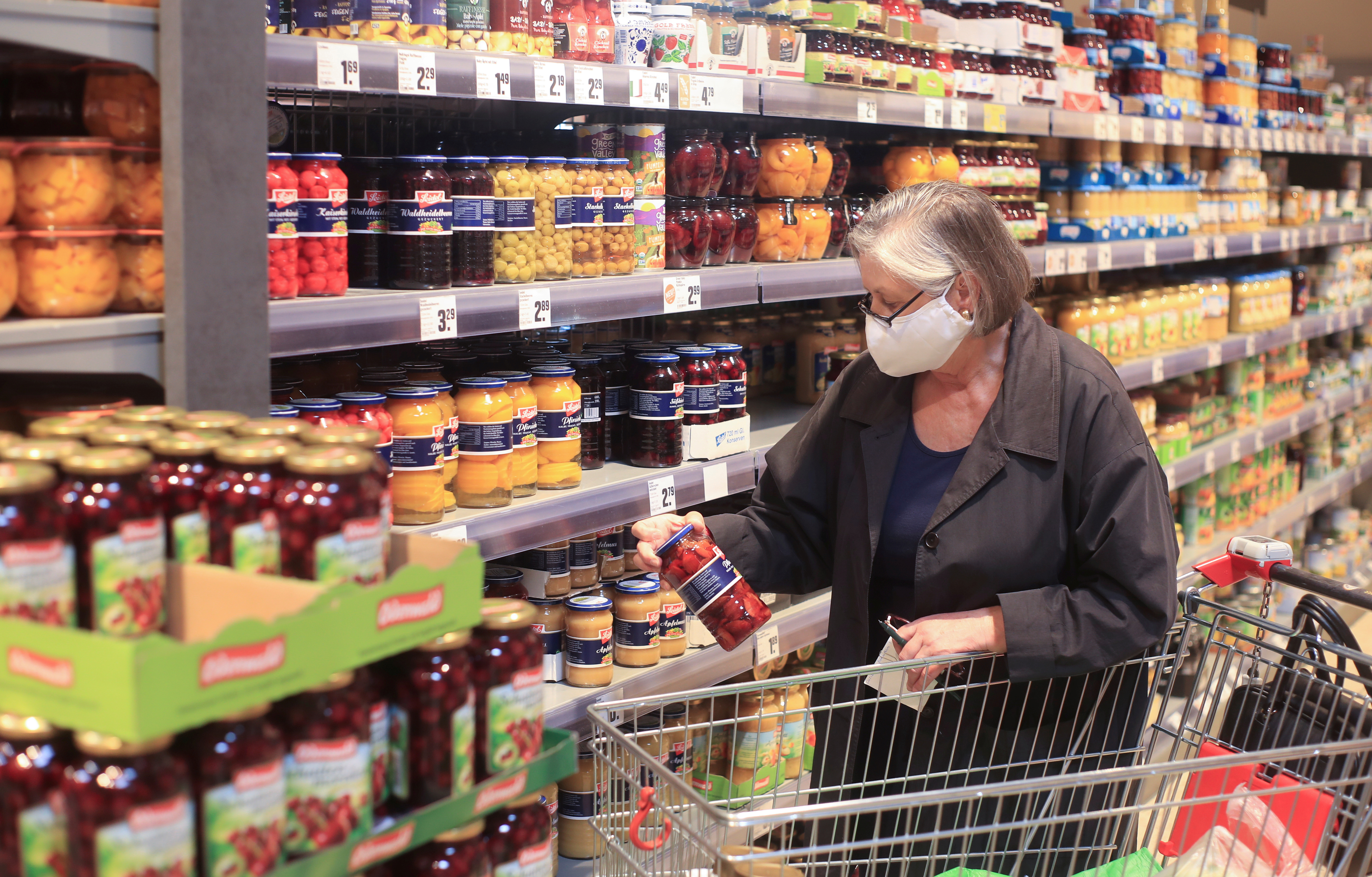 An elderly woman wearing a face mask shops in a supermarket, after the federal state of North Rhine-Westphalia decided to make wearing protective masks obligatory in shops and public transportation to fight the spread of the coronavirus disease (COVID-19), in Bad Honnef near Bonn,  Germany, April 27, 2020. REUTERS/Wolfgang Rattay/File Photo