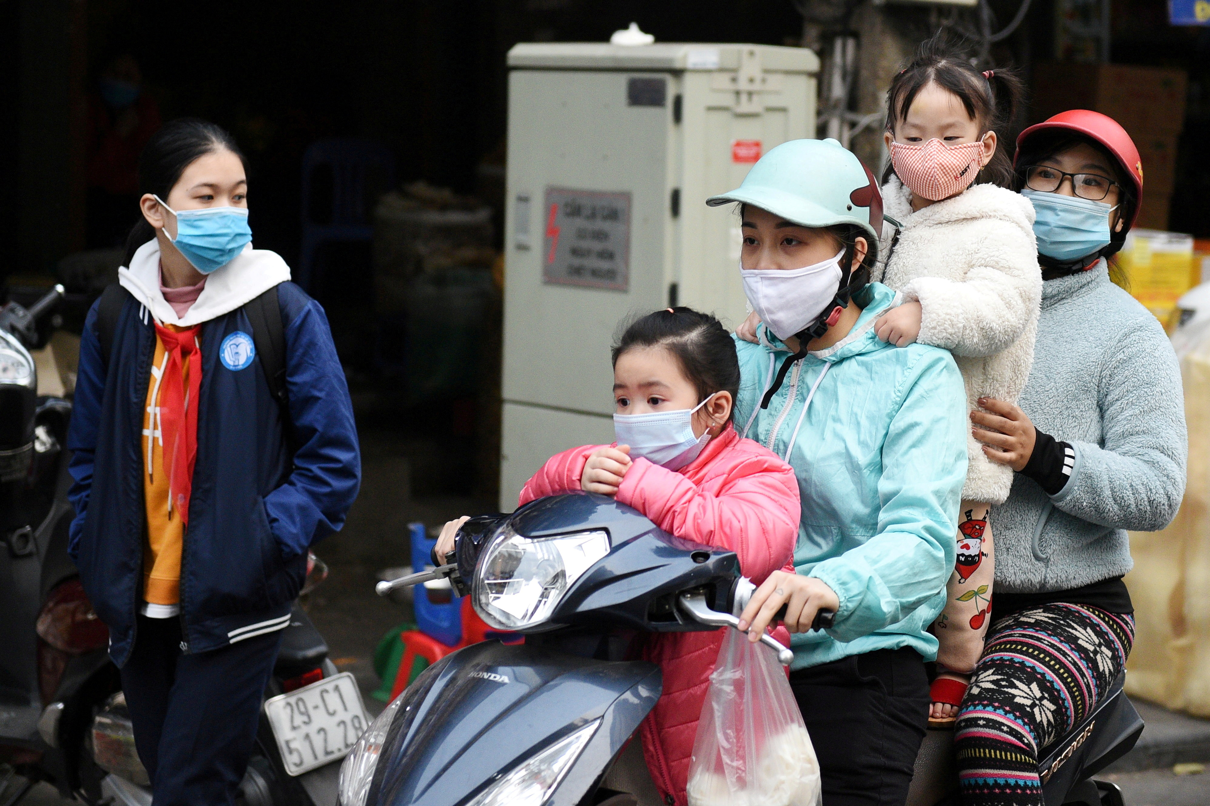 A family wears protective masks as they ride a motorbike in the street amid the coronavirus disease (COVID-19) outbreak in Hanoi, Vietnam, January 29, 2021. REUTERS/Thanh Hue