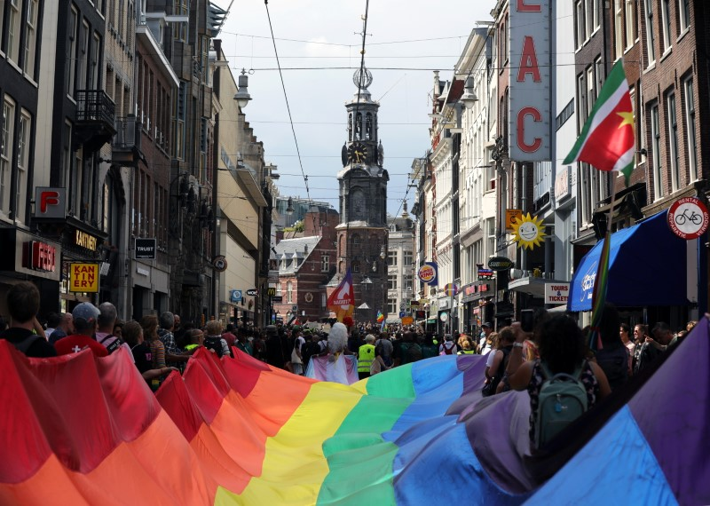 People carry a giant rainbow flag in the 25th gay pride parade in Amsterdam, Netherlands August 7, 2021. REUTERS/Eva Plevier