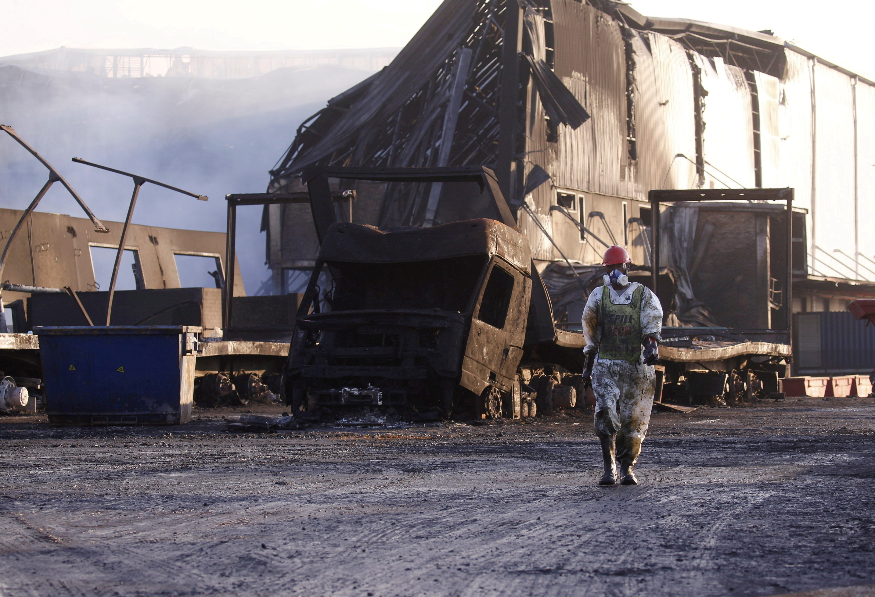 A member of a hazardous waste cleanup crew walks to clean up a warehouse which was burned during days of looting following the imprisonment of former South African President Jacob Zuma, in Durban, South Africa, July 17, 2021. REUTERS/Rogan Ward/File Photo