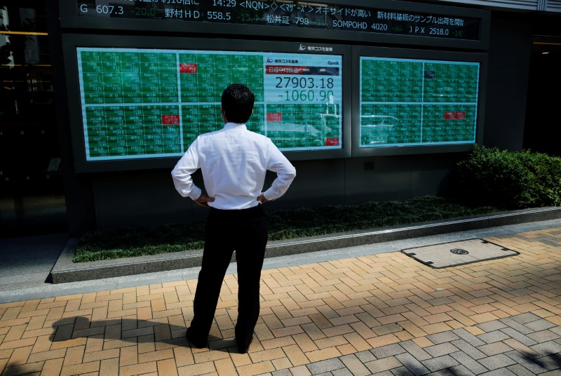 A man watches an electric board showing Nikkei index outside a brokerage at a business district in Tokyo, Japan, June 21, 2021.   REUTERS/Kim Kyung-Hoon/File photo