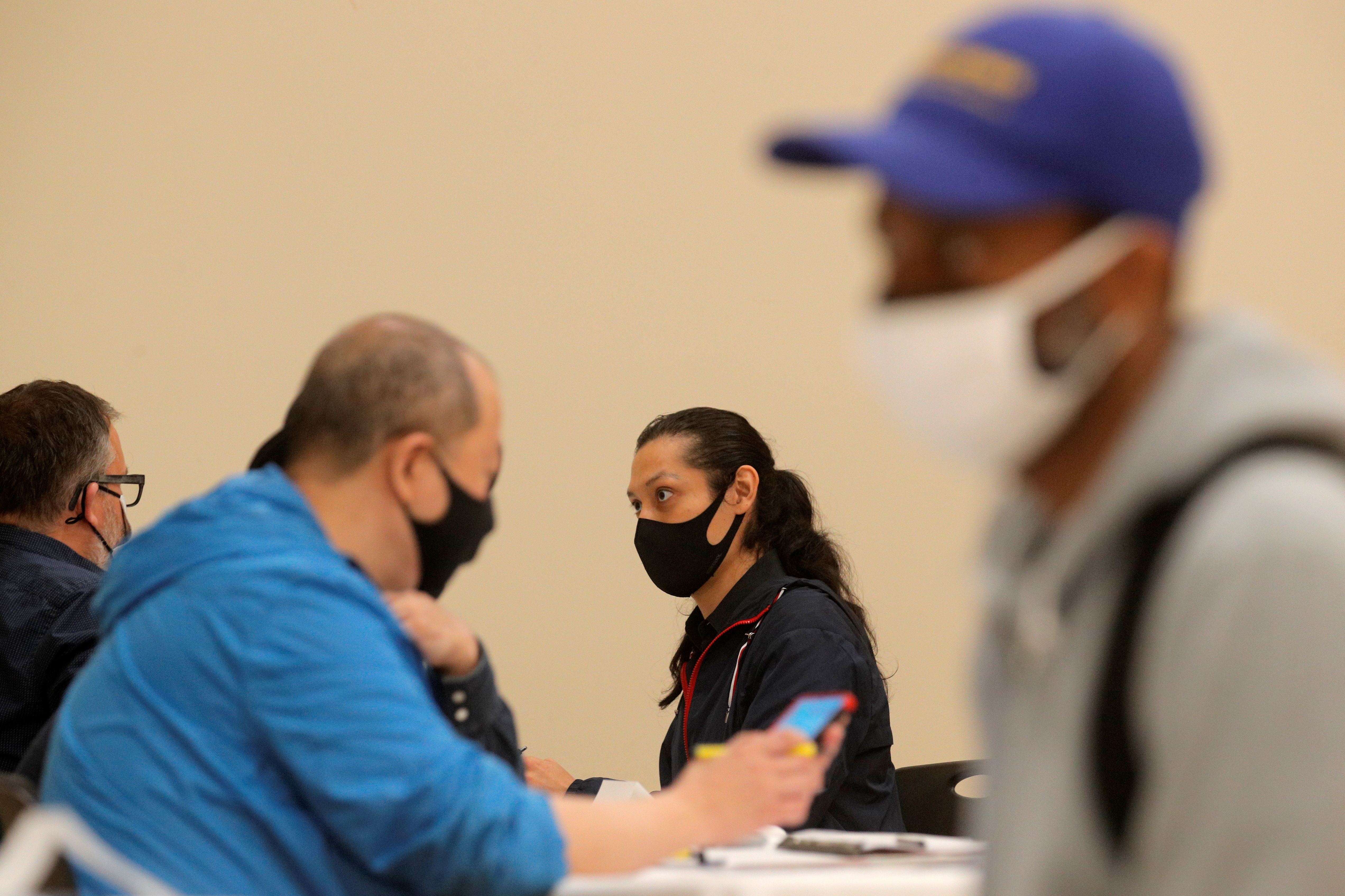 Applicants talk with recruiters during a restaurant job career fair organized by the industry group High Road Restaurants in New York City, U.S., May 13, 2021.  REUTERS/Brendan McDermid