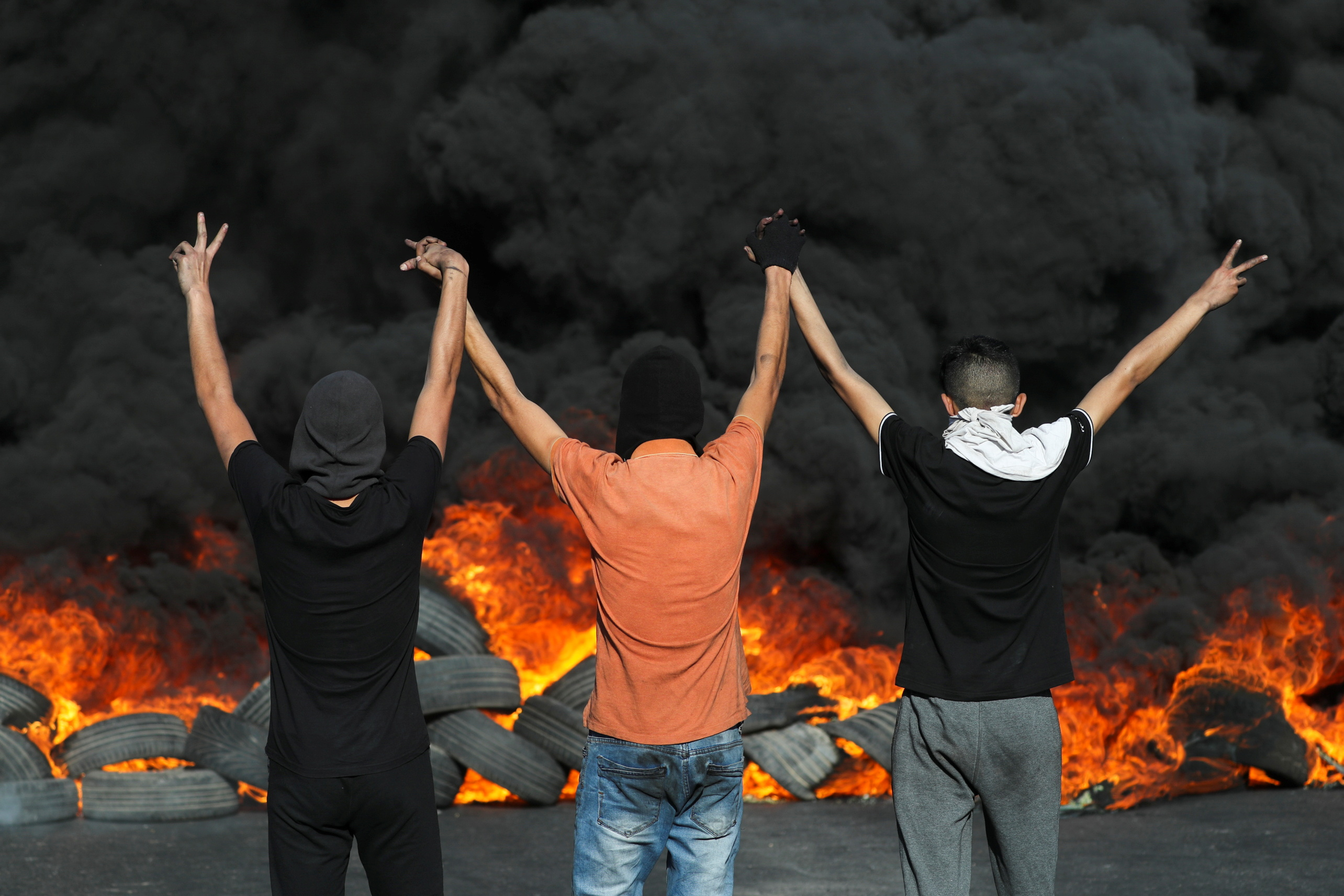 Palestinian demonstrators look at burning tires during a protest over tension in Jerusalem and Israel-Gaza escalation, in the Israeli-occupied West Bank, May 16, 2021. REUTERS/Ammar Awad