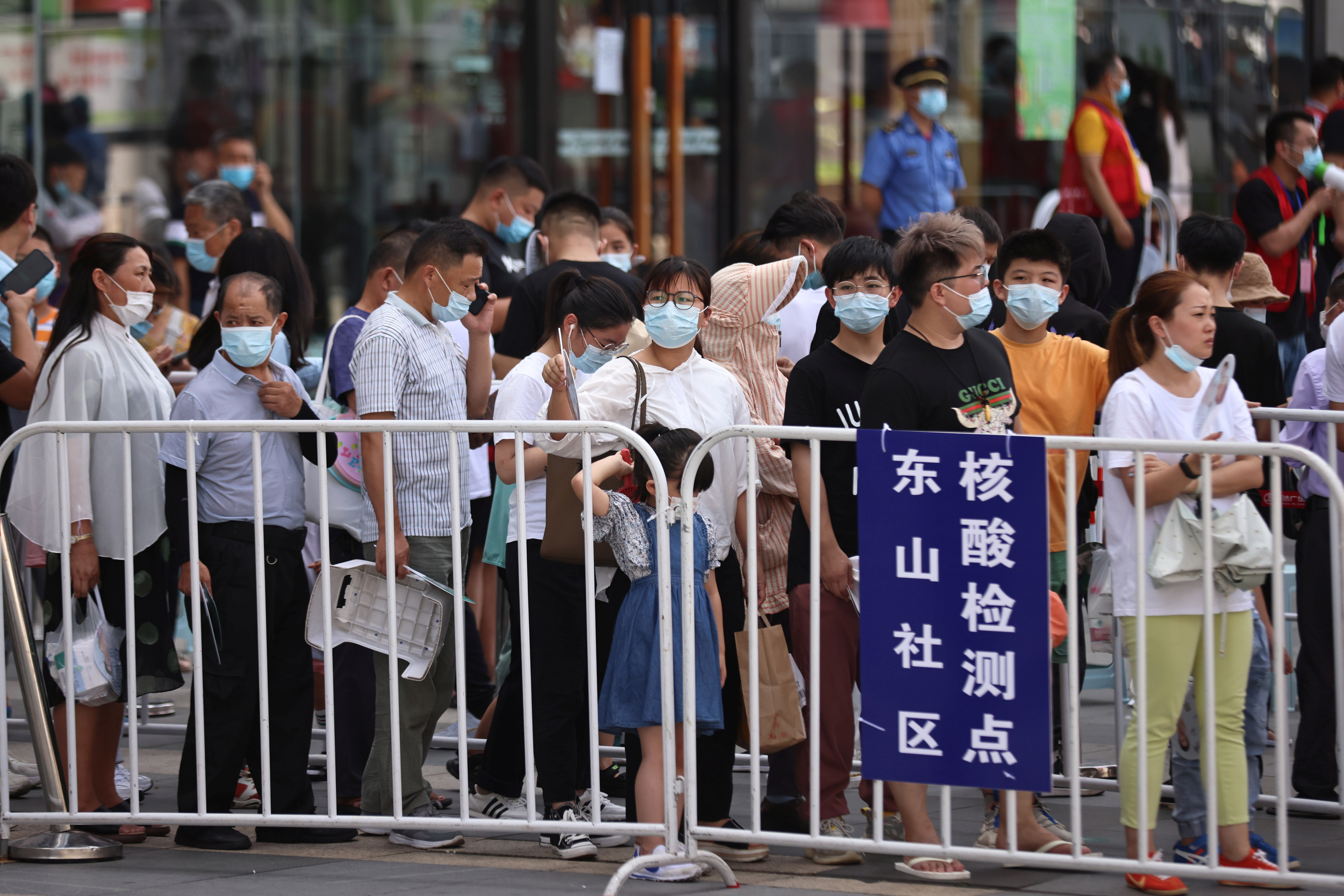 People line up at a makeshift nucleic acid testing site outside a shopping mall in Jiangning district, following new cases of the coronavirus disease (COVID-19) in Nanjing, Jiangsu province, China July 21, 2021. cnsphoto via REUTERS