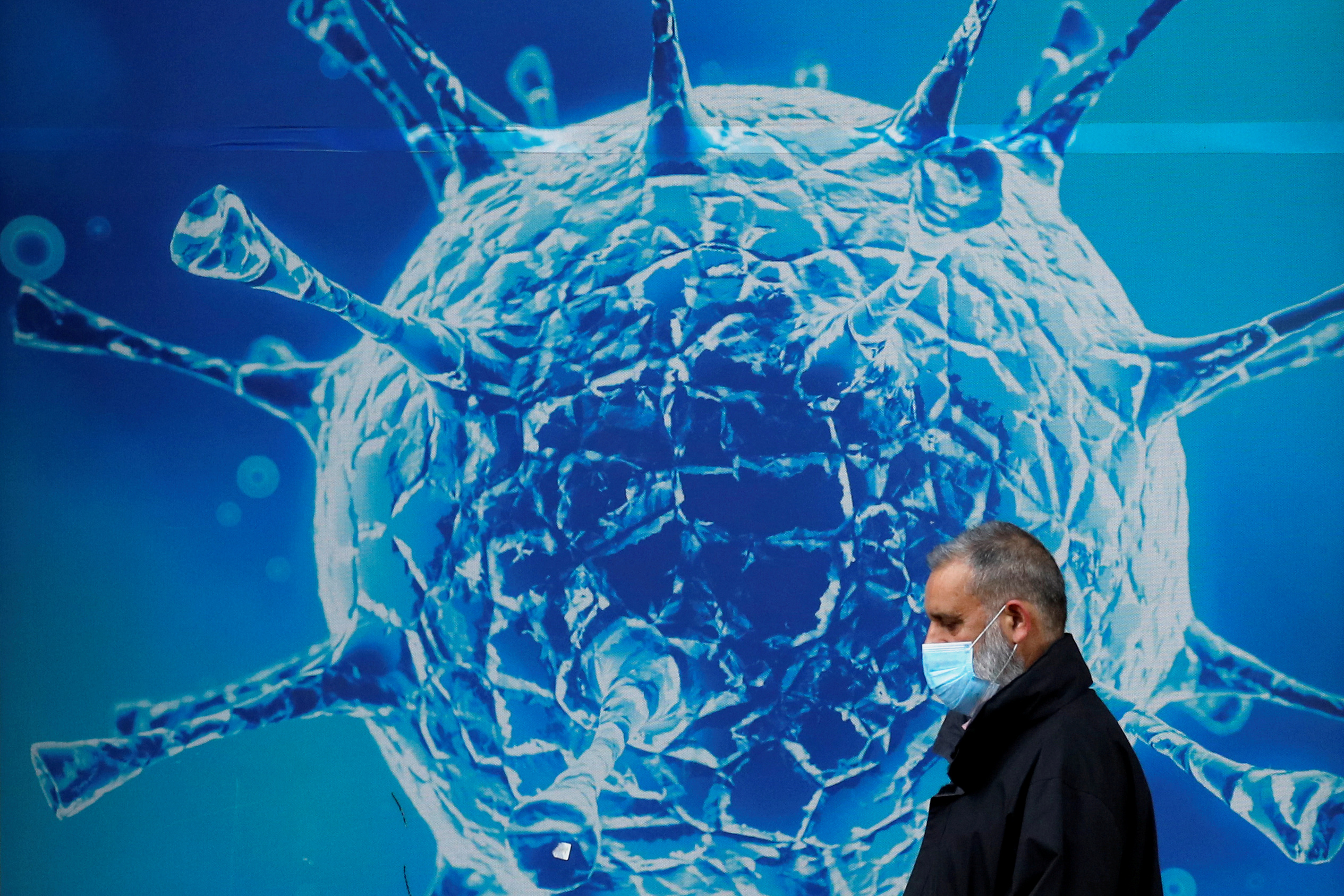 A man wearing a protective face mask walks past an illustration of a virus outside a regional science centre amid the coronavirus disease (COVID-19) outbreak, in Oldham, Britain August 3, 2020. REUTERS/Phil Noble
