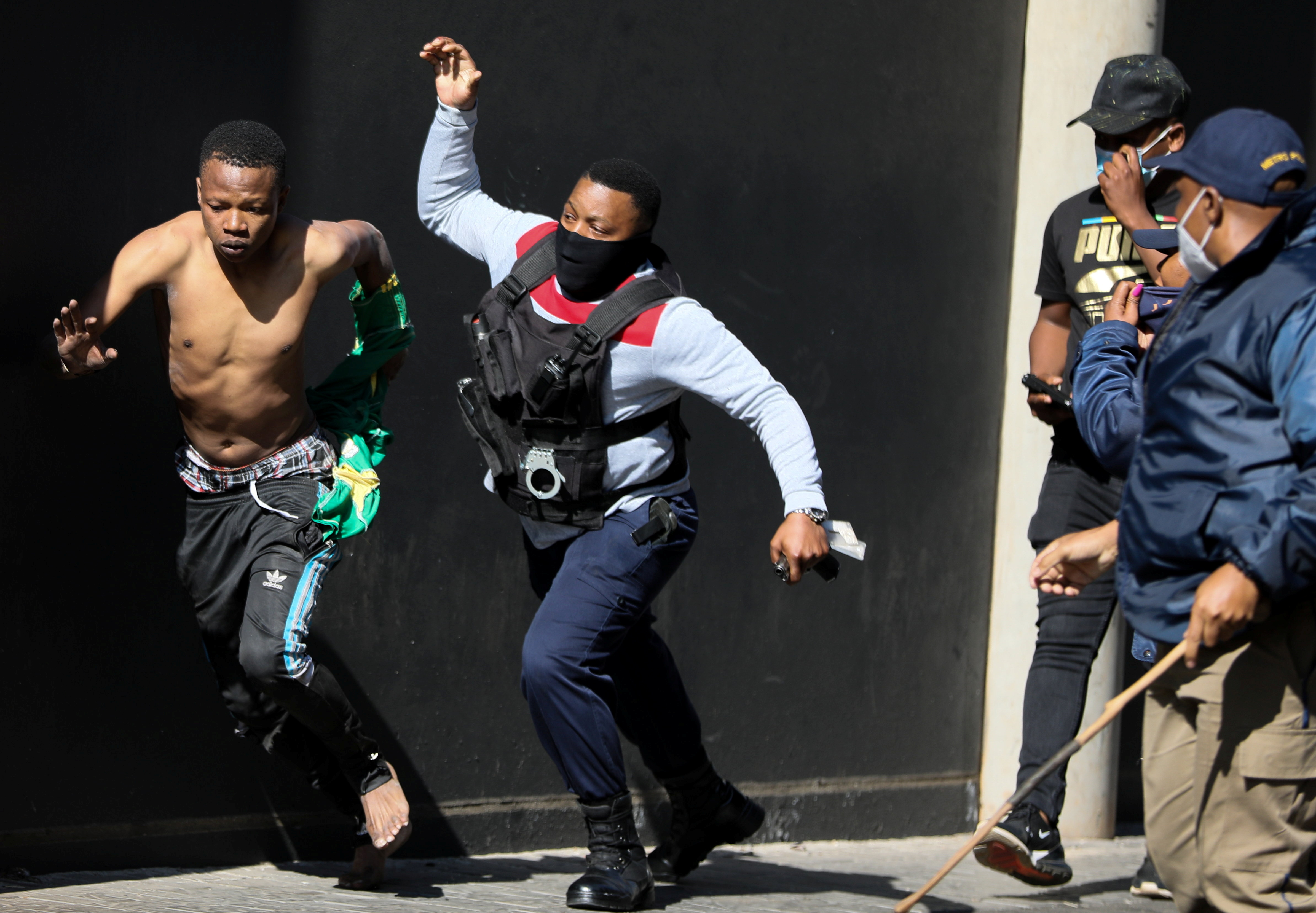 A police officer detains a suspect during a protest, as violence following the jailing of former South African President Jacob Zuma spread to the country's main economic hub in Johannesburg, South Africa, July 11, 2021. REUTERS/Sumaya Hisham