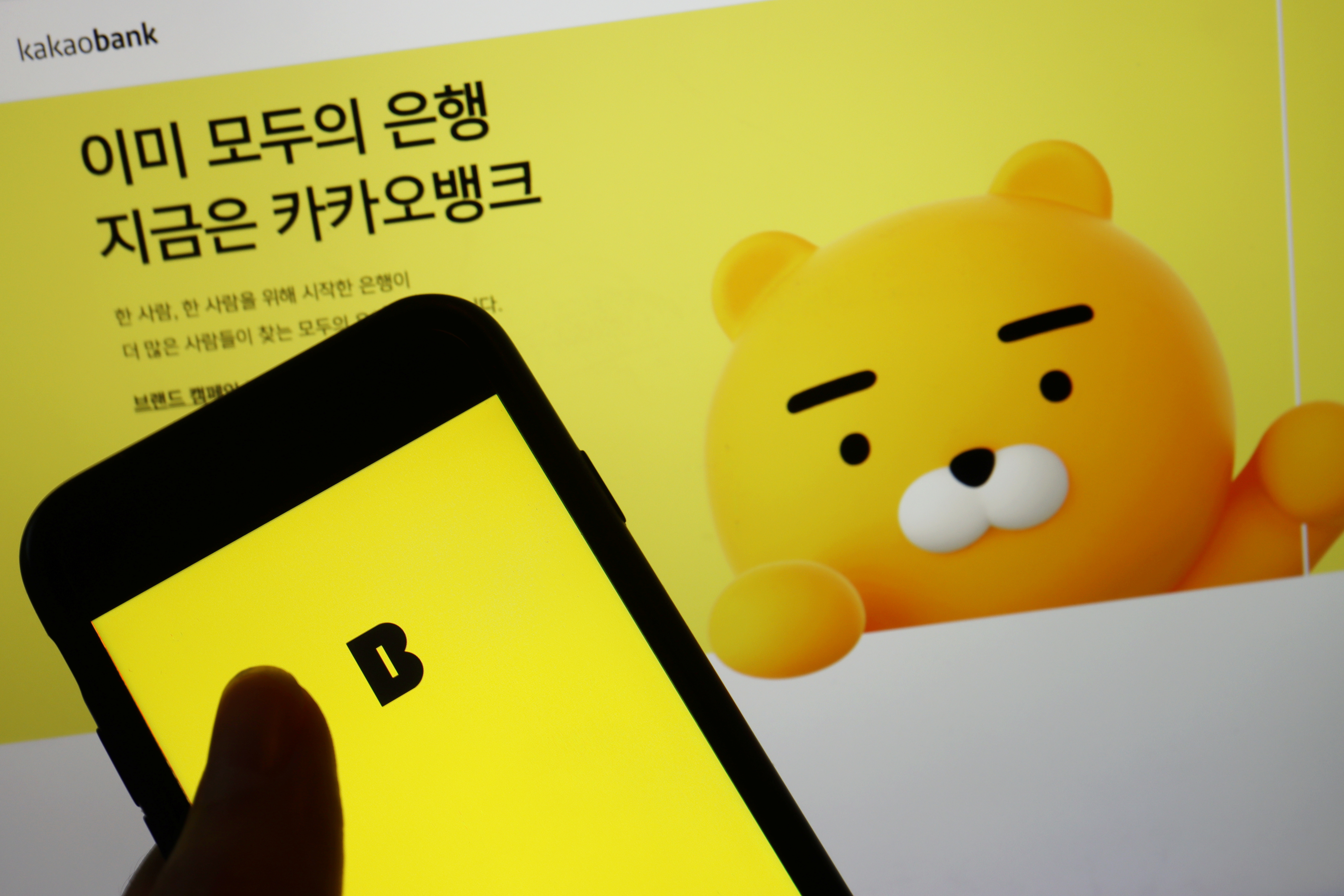 The Kakao Bank app is seen on a mobile phone screen displayed in front of the South Korean digital lender's website in this illustration picture taken August 6, 2021. REUTERS/Florence Lo/Illustration